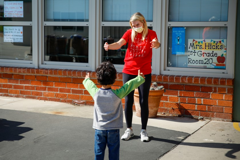 Observing physical distance, first-grade teacher Caitlin Hicks gives an air hug to Sid Solomon, 6, as she meets students one final time in June 2020, when students pick up schoolwork left behind after Center Street Elementary in El Segundo closed in March. (Jay L. Clendenin / Los Angeles Times)