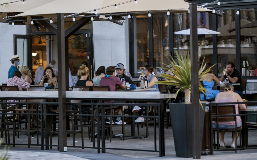 Unmasked customers enjoy the outdoor seating at the Marlin Bar in downtown Palm Springs amid the COVID-19 pandemic.(Gina Ferazzi/Los Angeles Times)