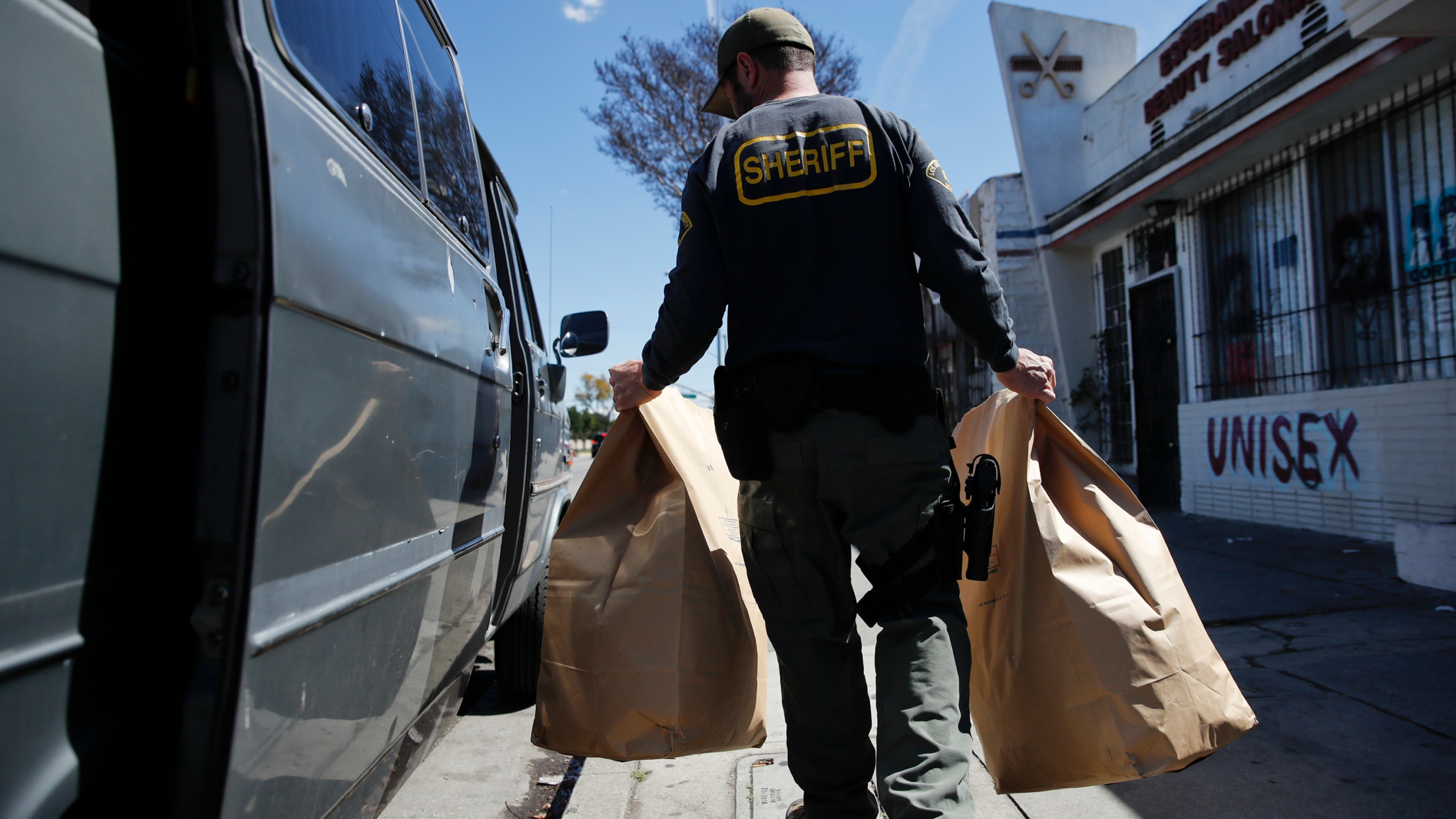 In this March 15, 2018 file photo, an undercover Los Angeles County sheriff's deputy loads two evidence bags into a van after raiding an illegal marijuana dispensary in Compton, one of many California cities where recreational marijuana use remains illegal. (AP Photo/Jae C. Hong, File)