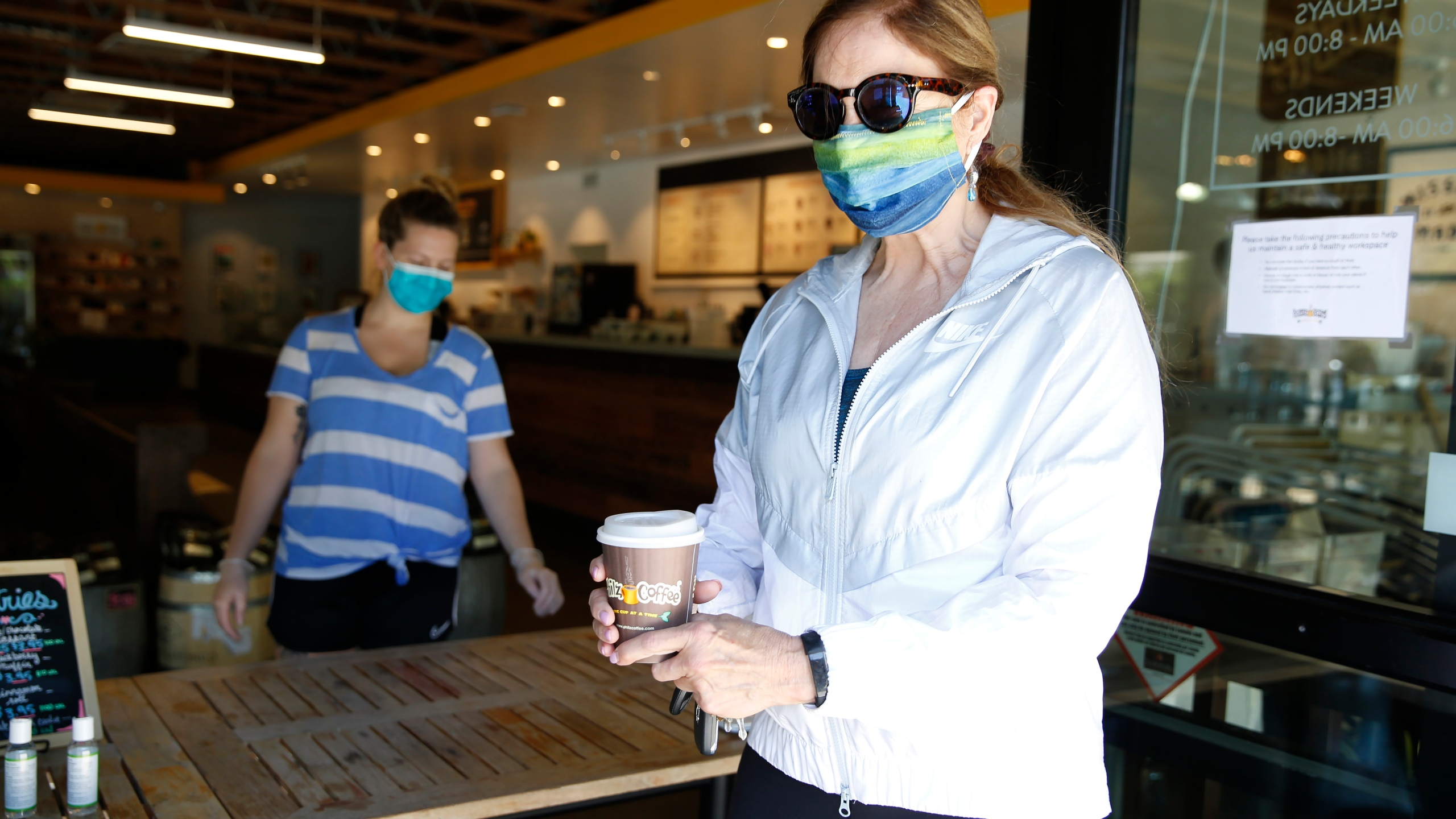 Barbara Meier, right, wears a face mask as picks up her drink order from Philz Coffee in Davis on April 27, 2020. (Rich Pedroncelli/Associated Press)