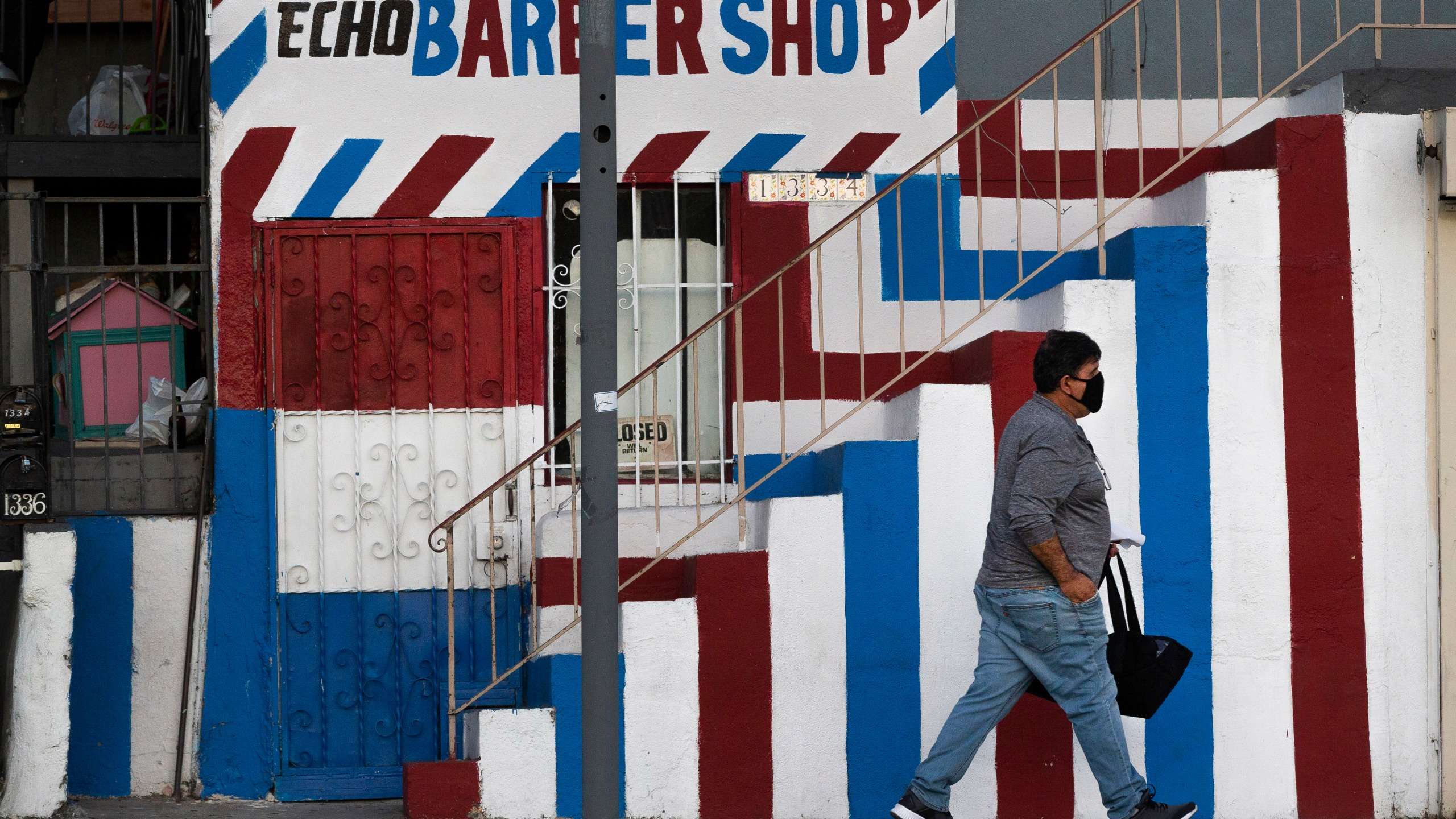 A pedestrian wears a mask as he walks past the closed Echo Barber Shop in Echo Park on May 8, 2020. (AP Photo/Damian Dovarganes)