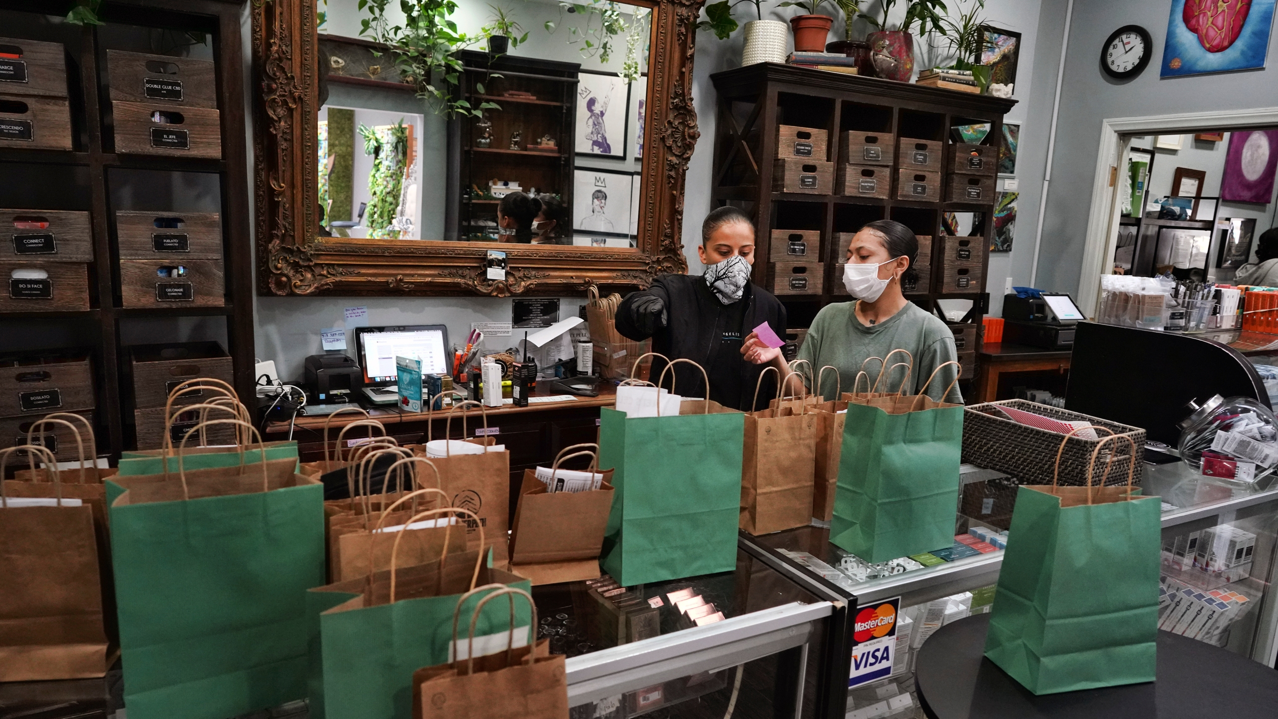 In this April 16, 2020, file photo, budtenders wearing protective masks prepare orders for customers to pick up at the Higher Path cannabis dispensary in the Sherman Oaks. (AP Photo/Richard Vogel, File)