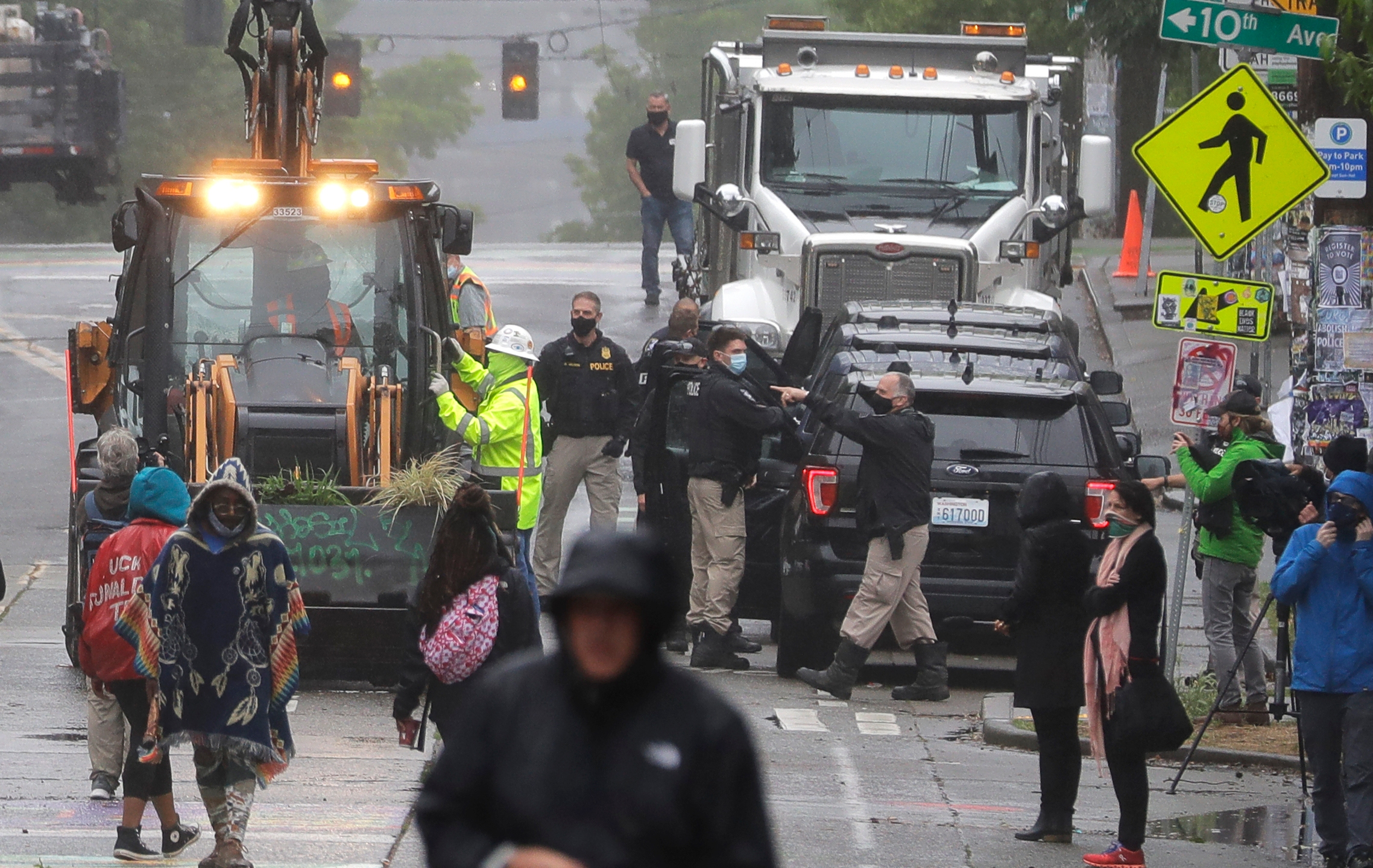Seattle Police, at right, look on as Department of Transportation workers remove barricades at the intersection of 10th Ave. and Pine St., Tuesday, June 30, 2020 at the CHOP (Capitol Hill Occupied Protest) zone in Seattle. (AP Photo/Ted S. Warren)