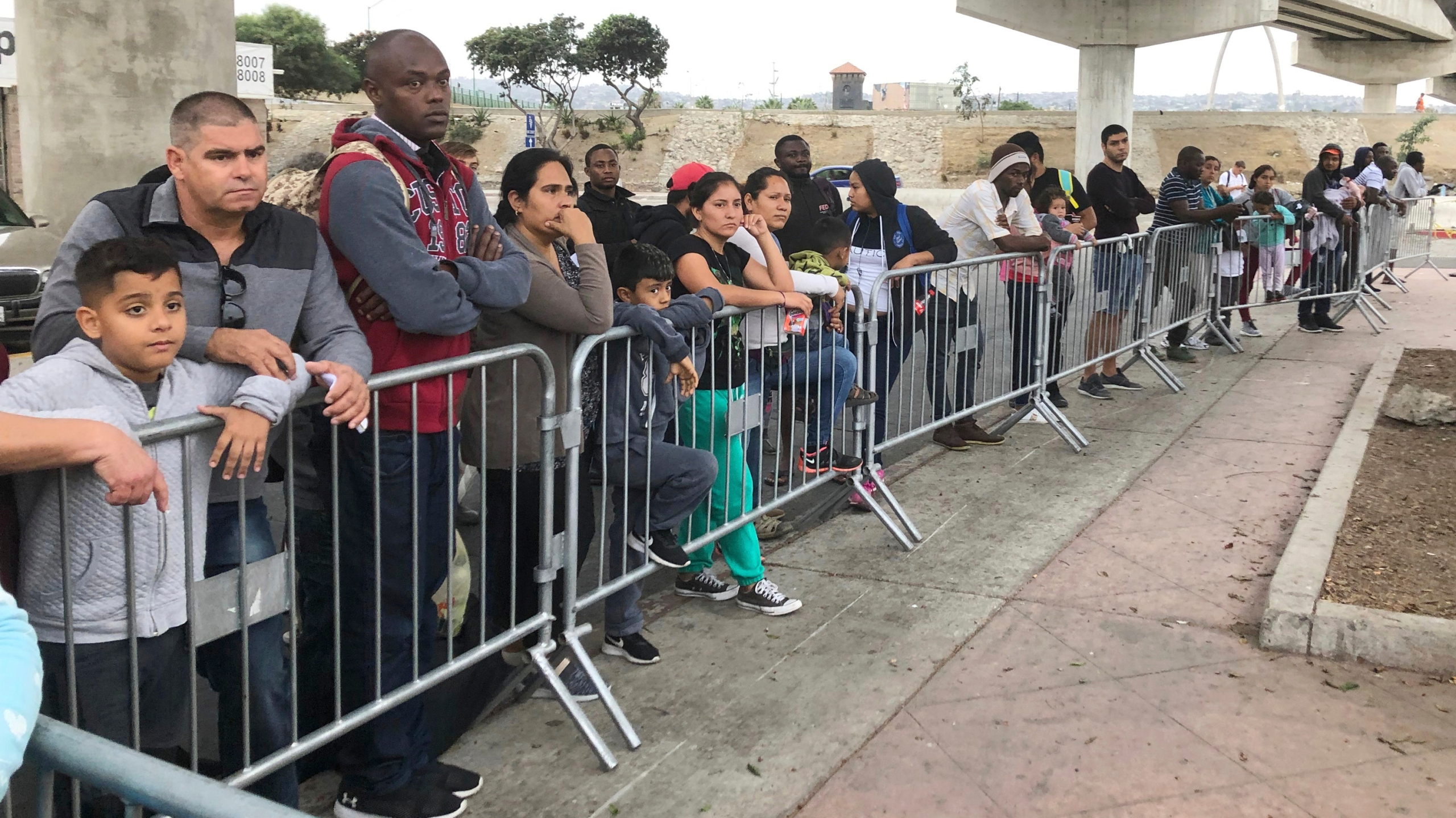 Asylum seekers in Tijuana, Mexico, listen to names being called from a waiting list to claim asylum at a border crossing in San Diego on Sept. 26, 2019. (AP Photo/Elliot Spagat,File)