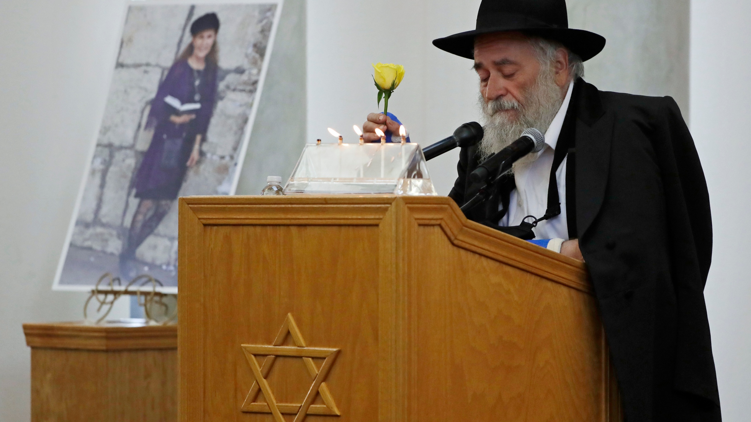 Yisroel Goldstein, Rabbi of Chabad of Poway, holds a yellow rose as he speaks at the funeral for Lori Gilbert-Kaye, who is pictured at left, in Poway on April 29, 2019. (AP Photo/Gregory Bull, File)