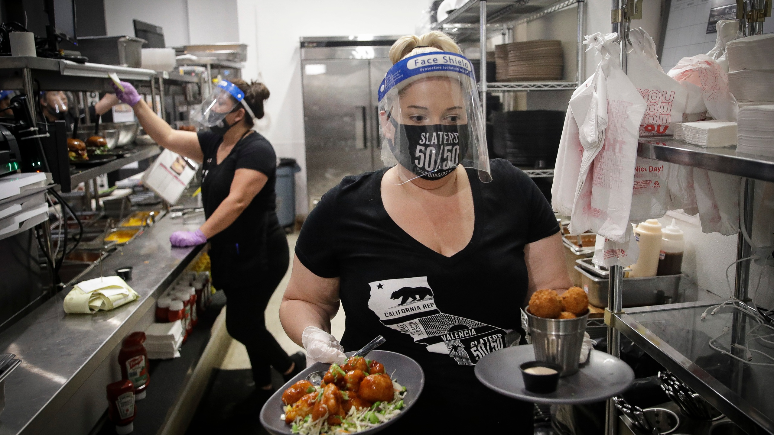 A waitress takes a food order from the kitchen at Slater's 50/50 on July 1, 2020, in Santa Clarita. (AP Photo/Marcio Jose Sanchez)