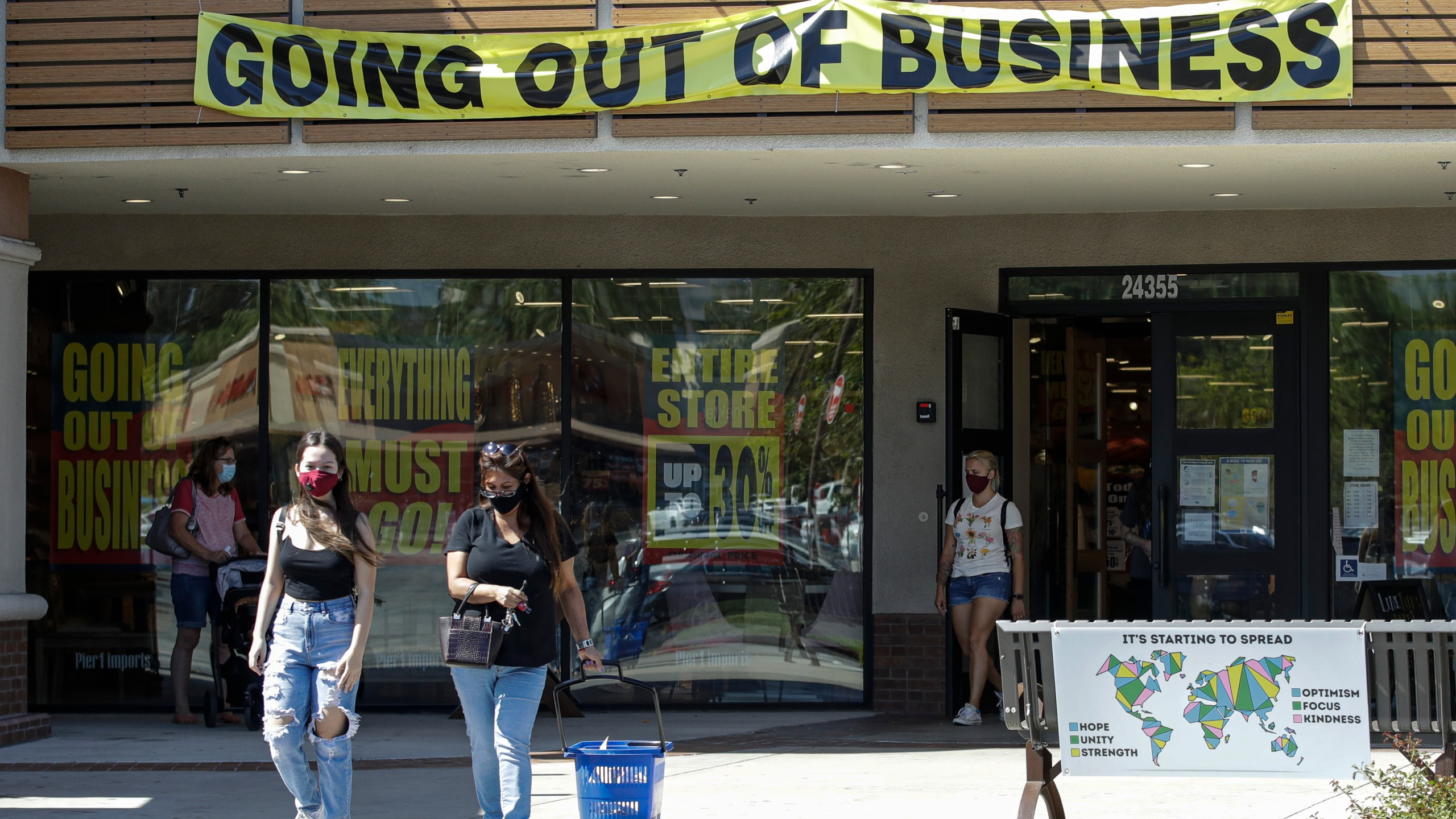 Shoppers walk outside of a Pier 1 Imports store as going out of business signs are posted amid the coronavirus pandemic Wednesday, July 1, 2020, in Santa Clarita. (AP Photo/Marcio Jose Sanchez)