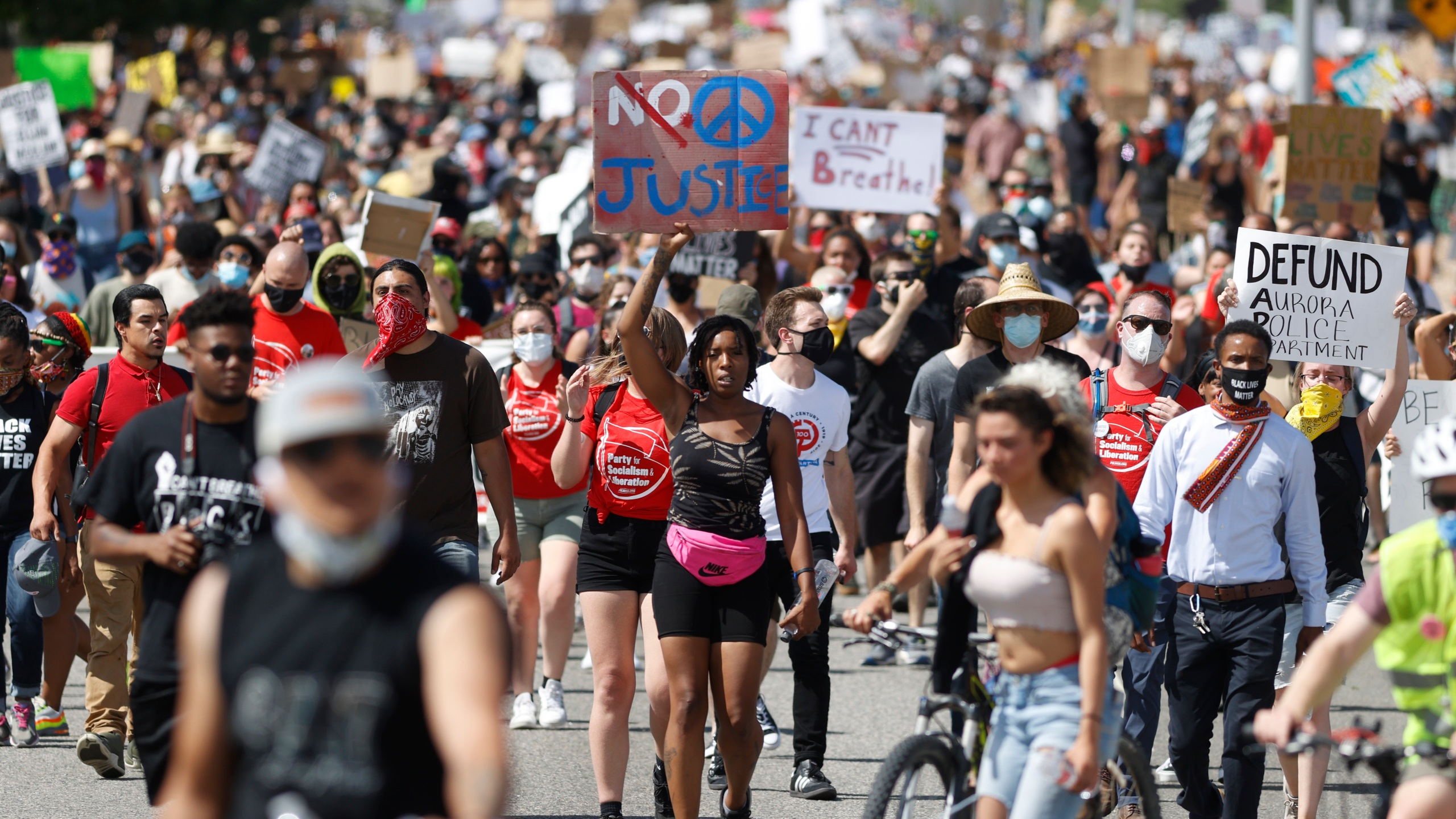 In this Saturday, June 27, 2020, file photo, demonstrators march down Sable Boulevard during a rally and march over the death of 23-year-old Elijah McClain, in Aurora, Colorado. (David Zalubowski / Associated Press)