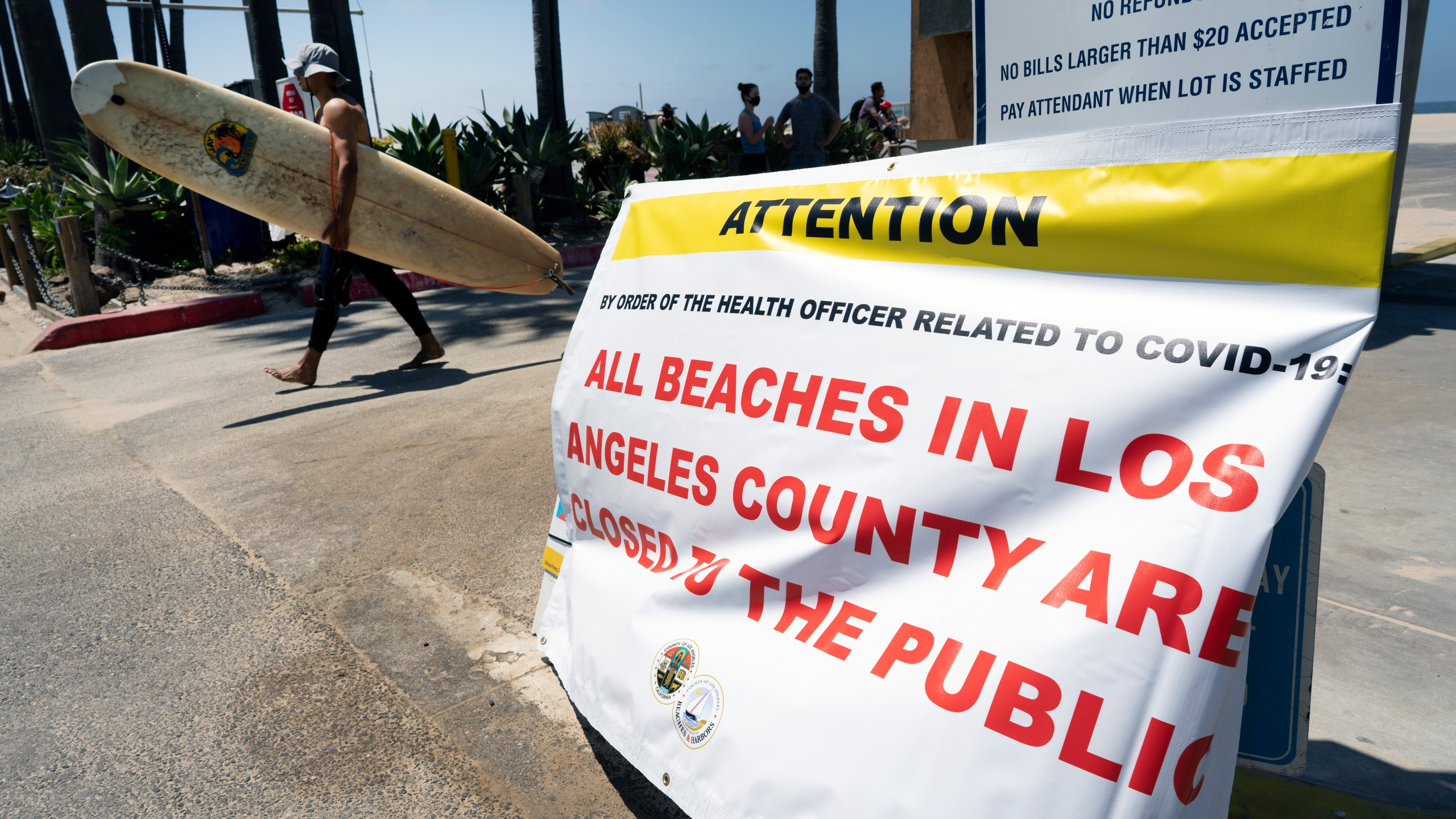 A surfer walks past a beach closed sign in Venice beach on Friday, July 3, 2020 in Los Angeles. The Los Angeles County Department of Public Health is ordering L.A. County beaches closed from July 3 through July 6, to prevent dangerous crowding that results in the spread of deadly COVID-19. California's governor is urging people to wear masks and skip Fourth of July family gatherings as the state's coronavirus tally rises. (AP Photo/Richard Vogel)
