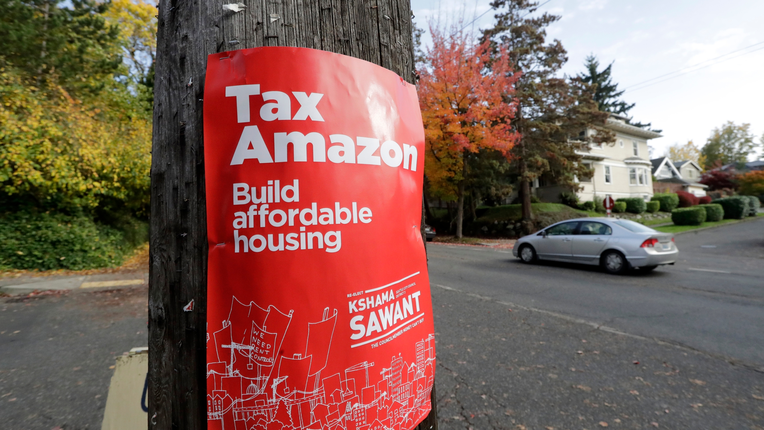 In this Oct. 23, 2019, file photo, a campaign poster for Seattle City Council incumbent candidate Kshama Sawant is posted outside her campaign headquarters in Seattle. The City Council on Monday, July 6, 2020, approved a new tax on big businesses two years after the council repealed a similar tax amid pressure from corporations such as Amazon. (Elaine Thompson/Associated Press)