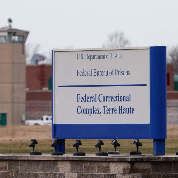 The guard tower flanks the sign at the entrance to the U.S. Penitentiary in Terre Haute, Indiana, on Dec. 10, 2019. (Michael Conroy / Associated Press)