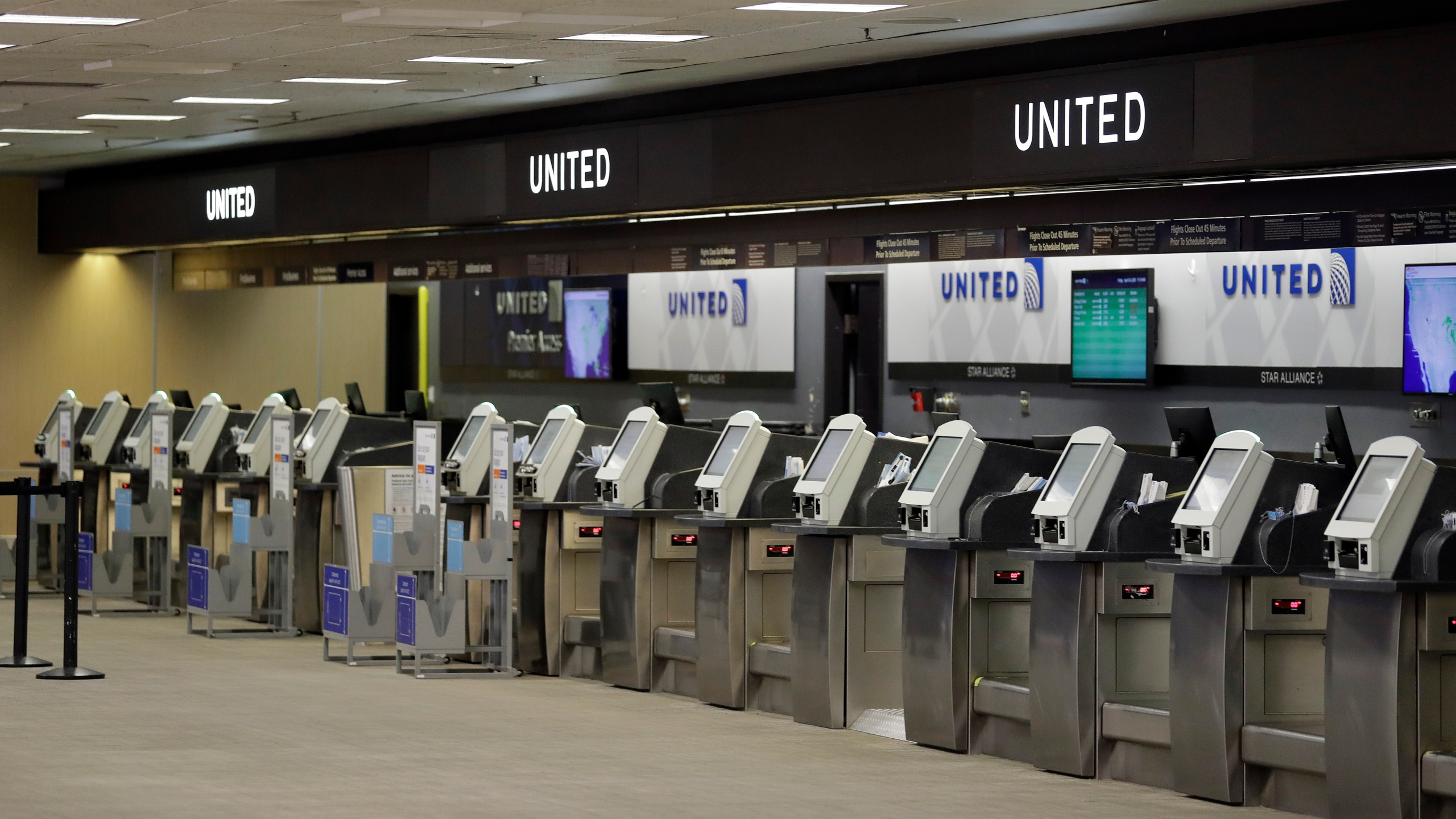In this April 24, 2020 file photo, empty United Airlines ticket machines are shown at the Tampa International Airport in Tampa, Fla. United United Airlines will send layoff warnings to 36,000 employees - nearly half its U.S. staff - in the clearest signal yet of how deeply the virus outbreak is hurting the airline industry. (AP Photo/Chris O'Meara, File)