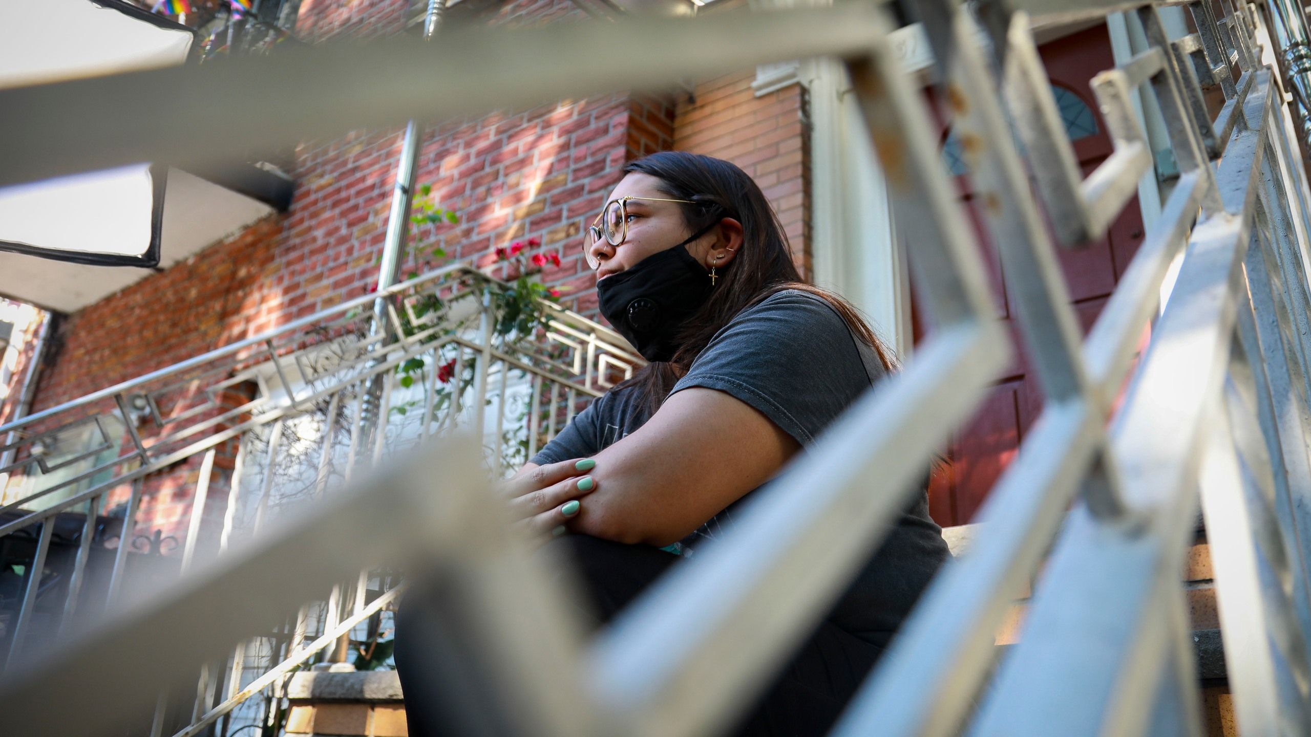 Natalia Afonso, 27, an international student from Brazil at Brooklyn College, sits on a stoop outside her home in New York during an interview on July 9, 2020. (Bebeto Matthews / Associated Press)