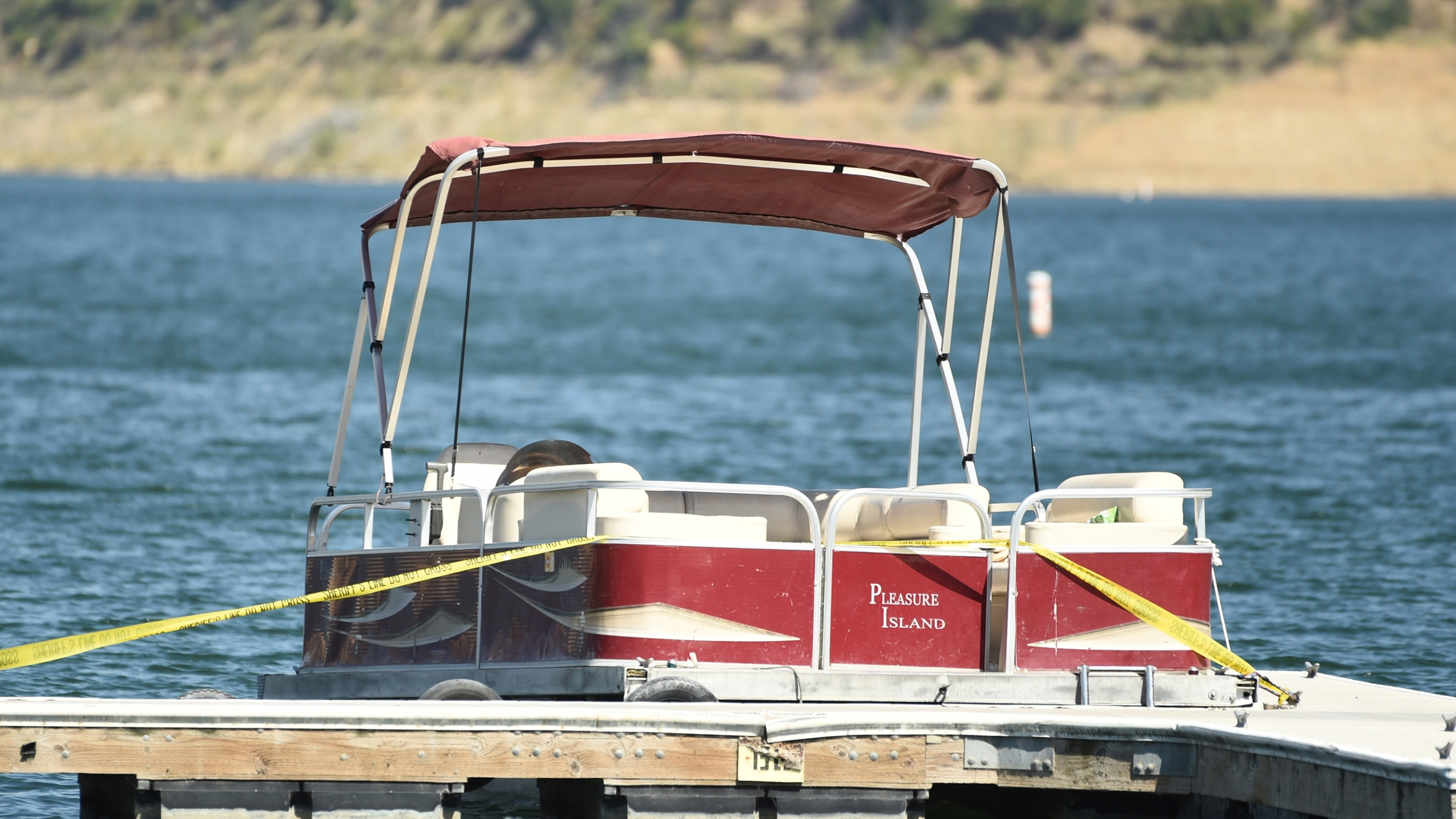 "A boat covered in caution tape rented by ""Glee"" actress Naya Rivera sits at a dock while members of Ventura County Sheriff's Office Underwater Search and Rescue Team search for the actress on Thursday, July 9, 2020, at Lake Piru in Los Padres National Forest, northwest of Los Angeles. (AP Photo/Chris Pizzello)"