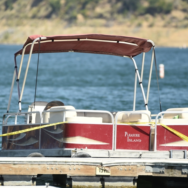 """A boat covered in caution tape rented by """"Glee"""" actress Naya Rivera sits at a dock while members of Ventura County Sheriff's Office Underwater Search and Rescue Team search for the actress on Thursday, July 9, 2020, at Lake Piru in Los Padres National Forest, northwest of Los Angeles. (AP Photo/Chris Pizzello)"""