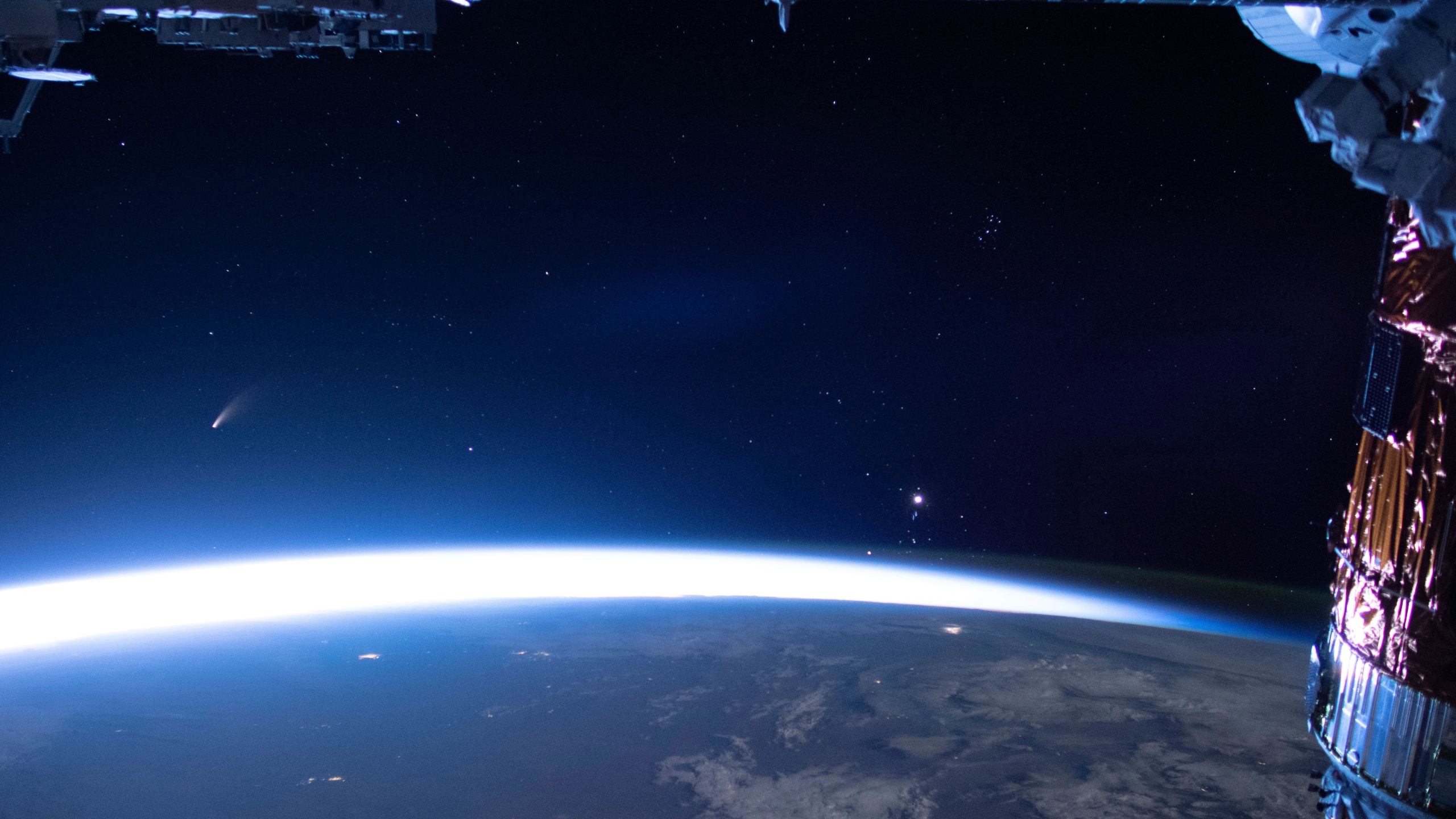 In this image released by NASA, Comet Neowise, left, is seen in the eastern horizon above Earth in this image taken from the International Space Station on Sunday, July 5, 2020. (NASA via AP)