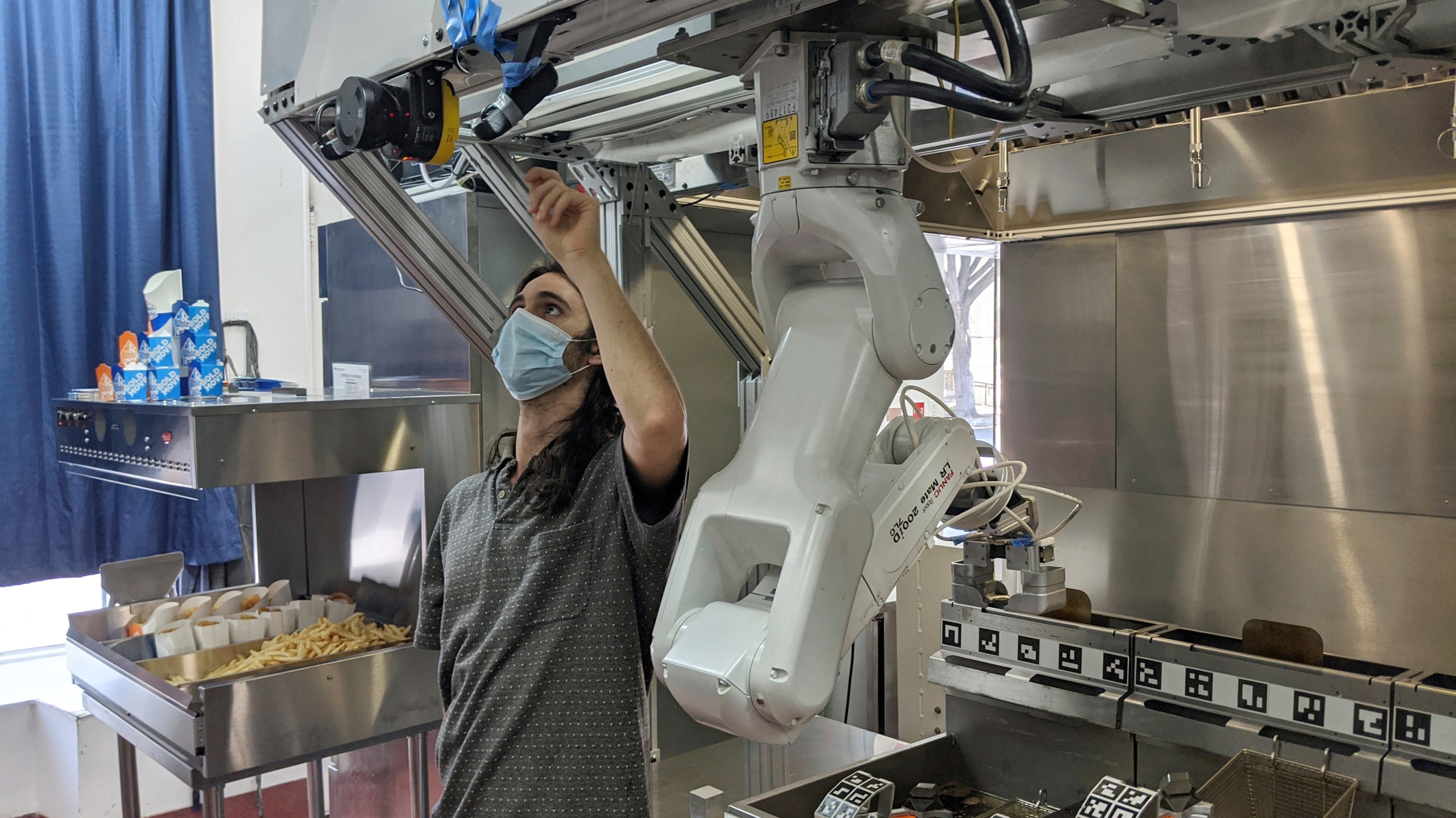 A technician makes an adjustment to a robot at Miso Robotics' White Castle test kitchen in Pasadena on July 9, 2020. (Miso Robotics via AP)