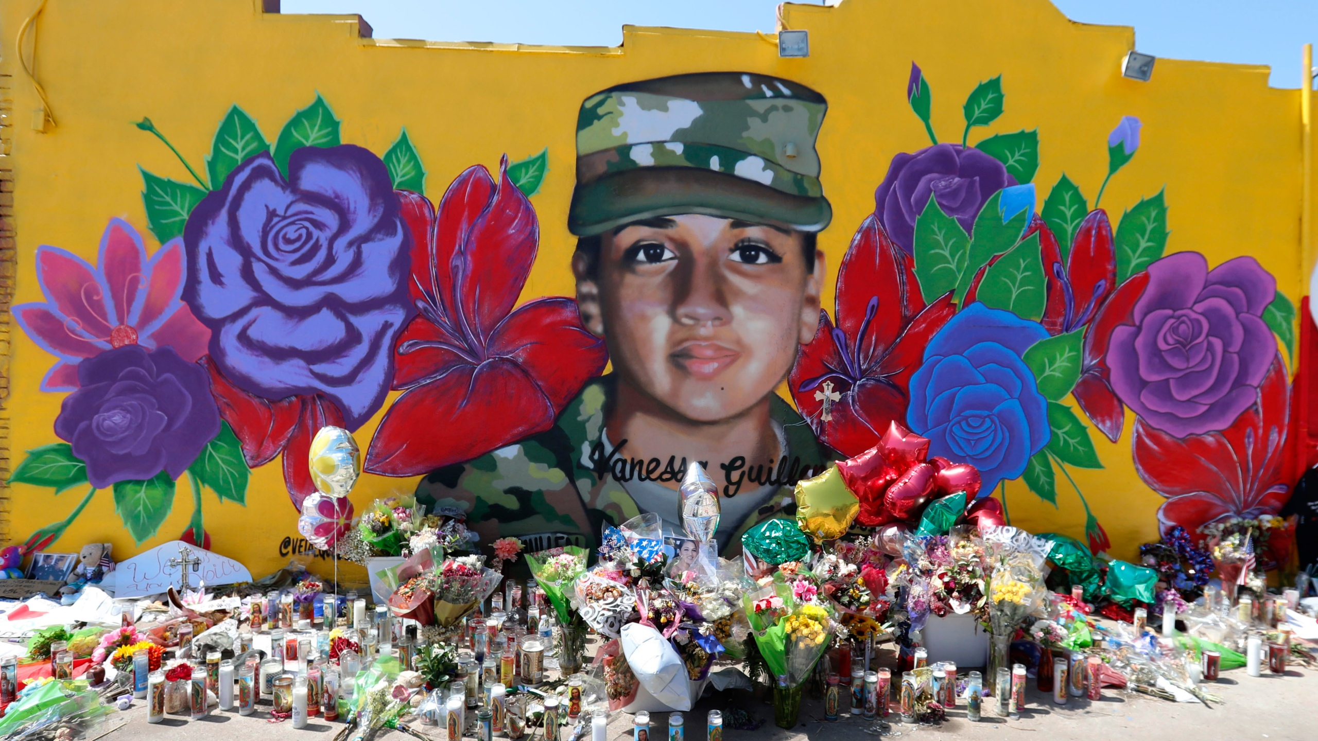 Offerings sit in front of a mural of slain Army Spc. Vanessa Guillen painted on a wall in the south side of Fort Worth, Texas on July 11, 2020. (AP Photo/LM Otero)