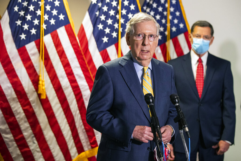 In this June 30, 2020, file photo, Senate Majority Leader Mitch McConnell, R-Ky., with Sen. John Barrasso, R-Wyo., speaks to reporters following a GOP policy meeting on Capitol Hill in Washington. President Donald Trump's push to reopen schools is being complicated by a split within his ranks over how to do it. Some advisers are advocating for a massive federal expenditure to make campuses safe. This comes Congress is compiling the next COVID-19 relief bill. McConnell said July 13 schooling will be a priority in the coming package. (AP Photo/Manuel Balce Ceneta, File)