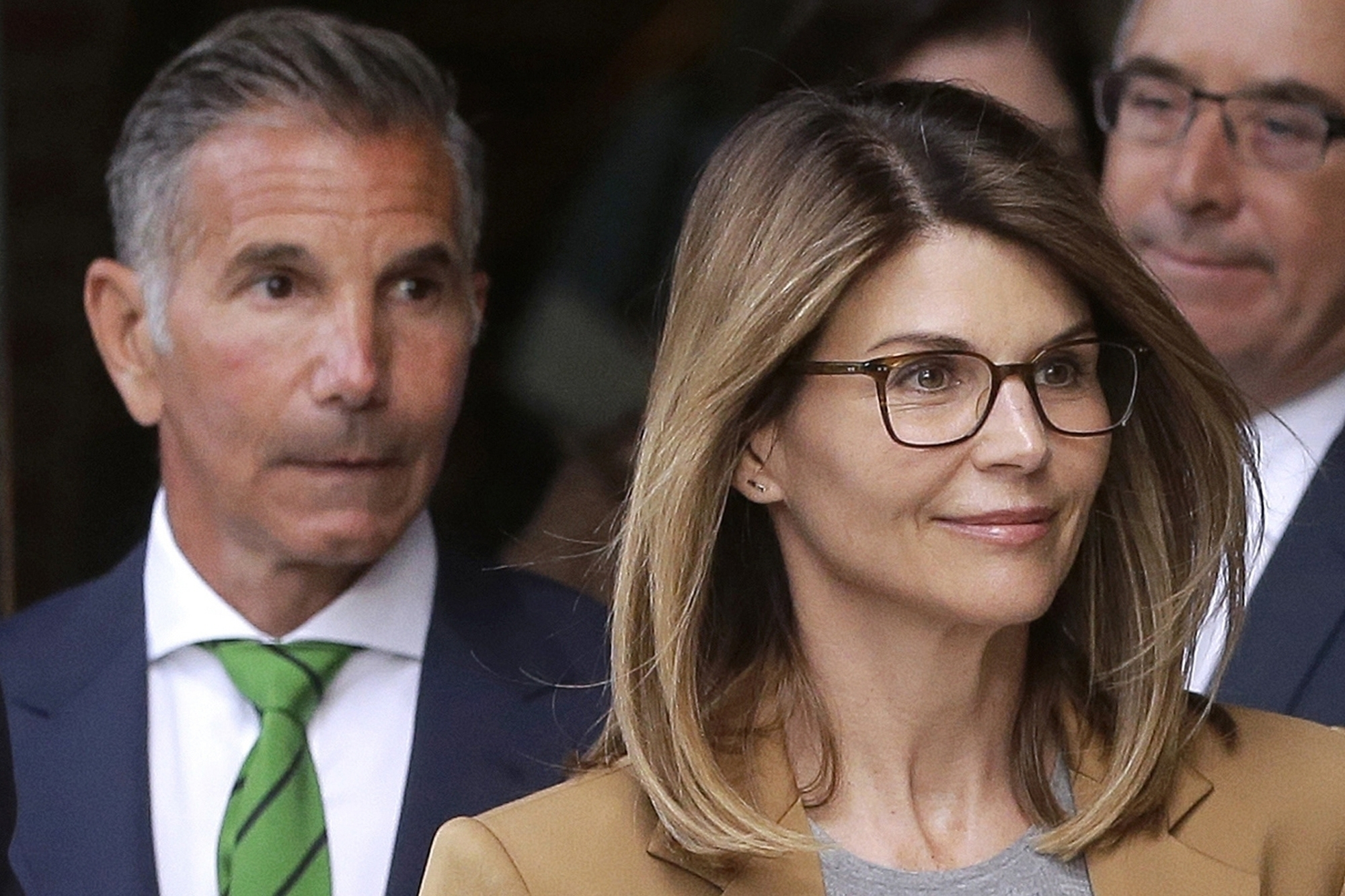 Actress Lori Loughlin, front, and her husband, clothing designer Mossimo Giannulli, left, depart federal court in Boston after a hearing in a nationwide college admissions bribery scandal on April 3, 2019. (AP Photo/Steven Senne, File)