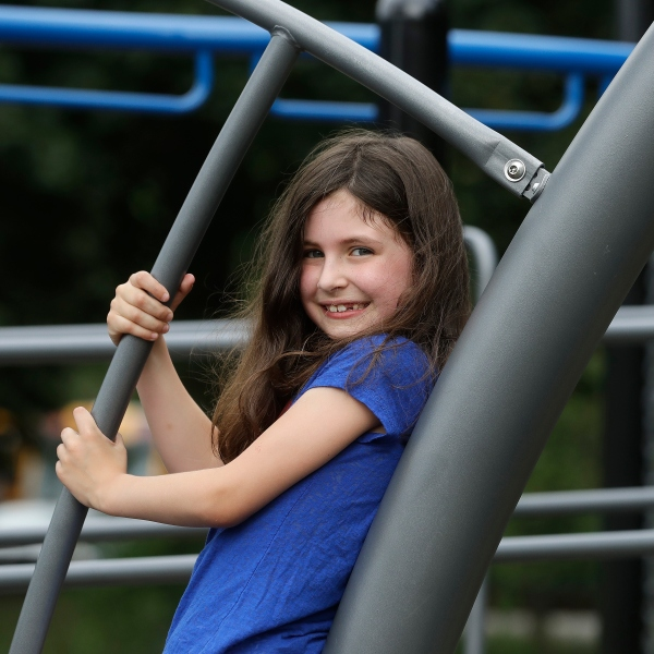 Sophia Garabedian, 6, of Sudbury, Massachusetts, who contracted Eastern Equine Encephalitis in 2019, stands for a photograph on a playground on July 8, 2020, in Sudbury. (AP Photo/Steven Senne)