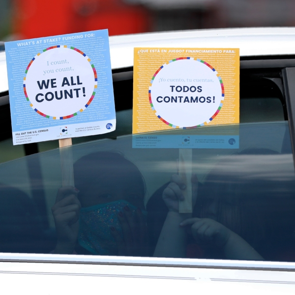 Two young children hold signs through the car window that make reference to the 2020 U.S. Census as they wait in the car with their family at an outreach event in Dallas on June 25, 2020. (AP Photo/Tony Gutierrez, File)