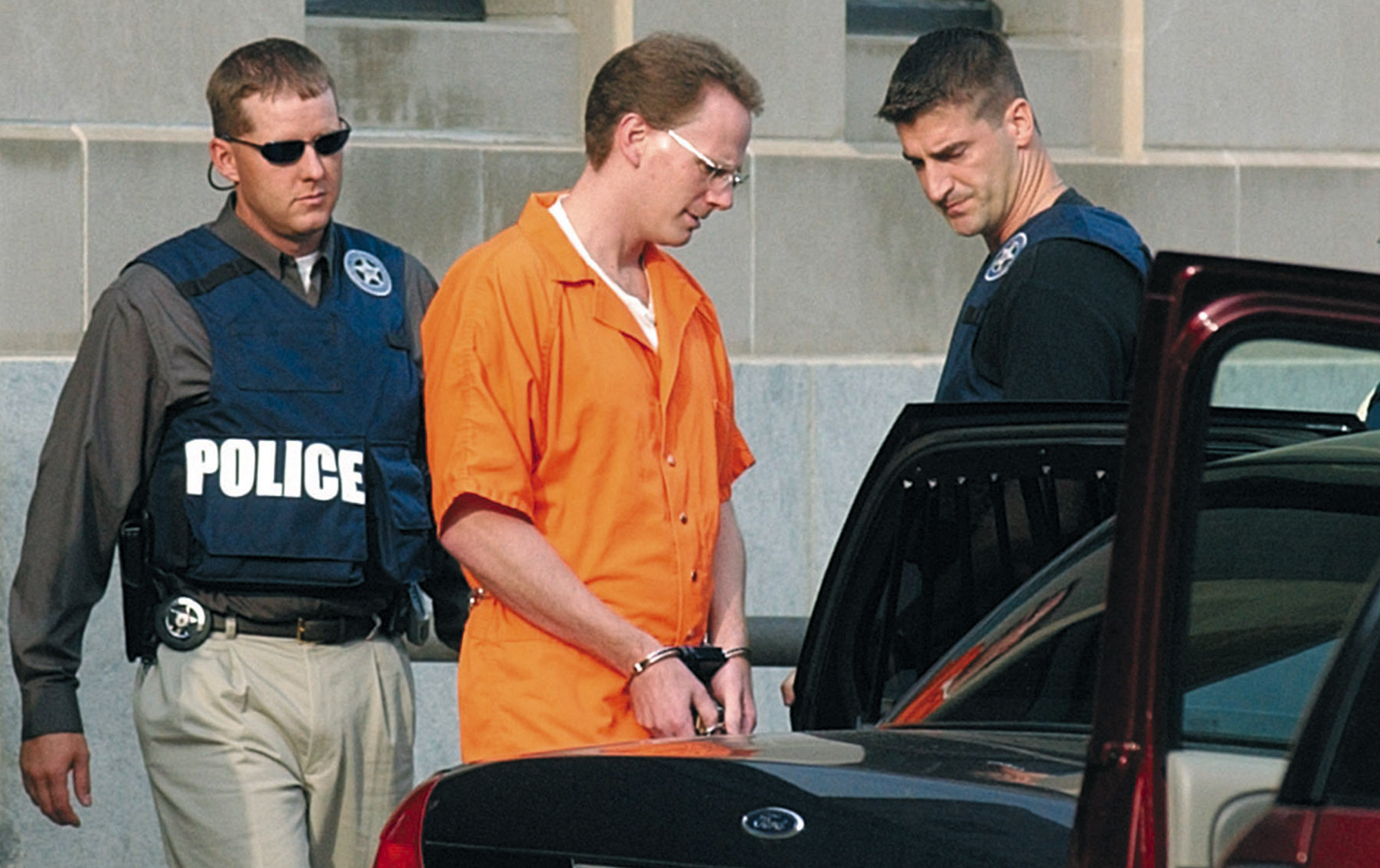 In this Aug. 18, 2004 file photo, Dustin Honken is led by federal marshals to a waiting car after the second day of jury selection in federal court in Sioux City, Iowa. (Tim Hynds / Sioux City Journal via Associated Press)