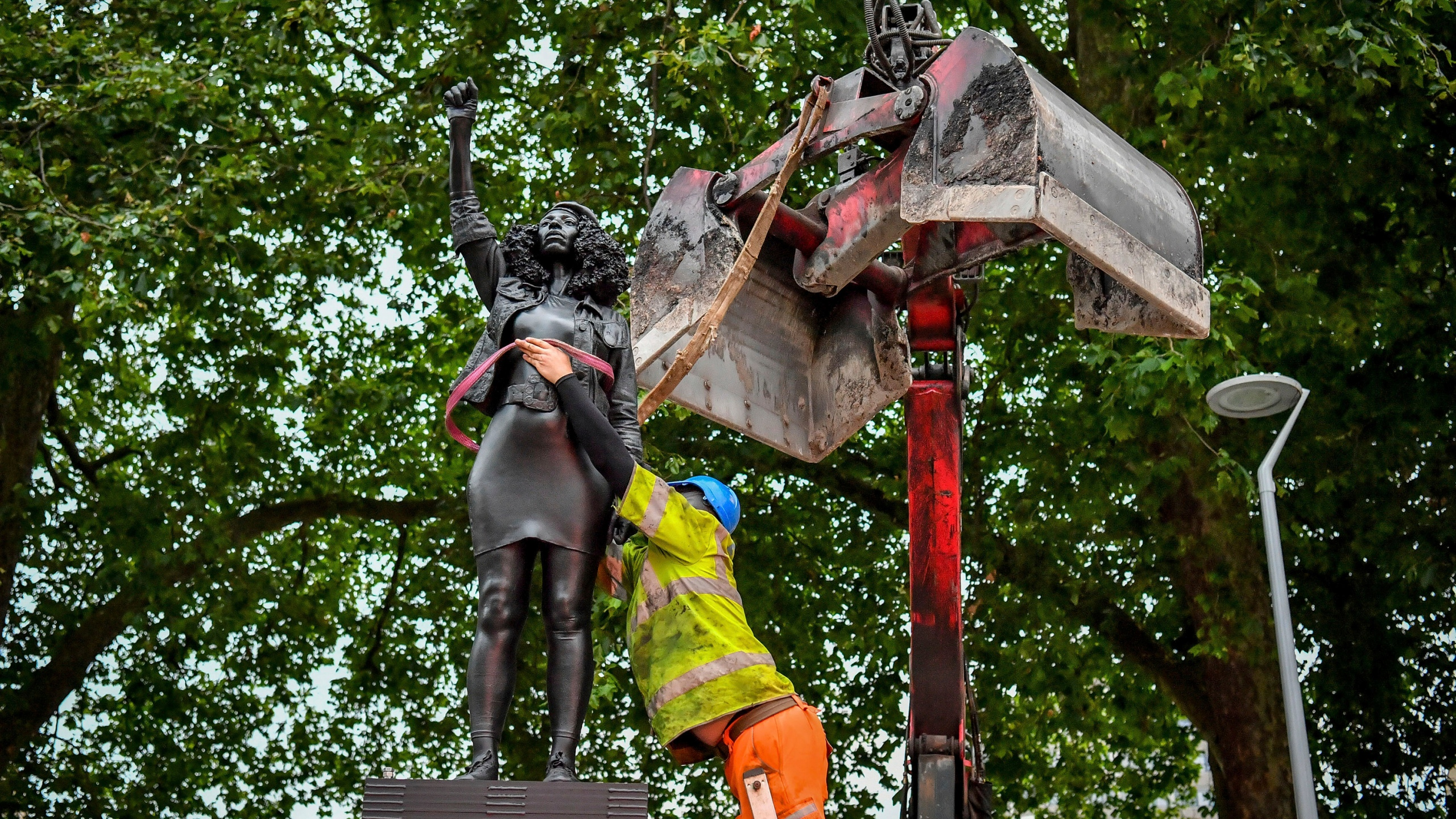 """A contractor uses ropes to secure the statue """"A Surge of Power (Jen Reid) 2020"""" by artist Marc Quinn, which had been installed on the site of the fallen statue of the slave trader Edward Colston, as they prepare to remove and load it into a recycling and skip hire lorry, in Bristol on July 16, 2020. (Ben Birchall/PA via AP)"""