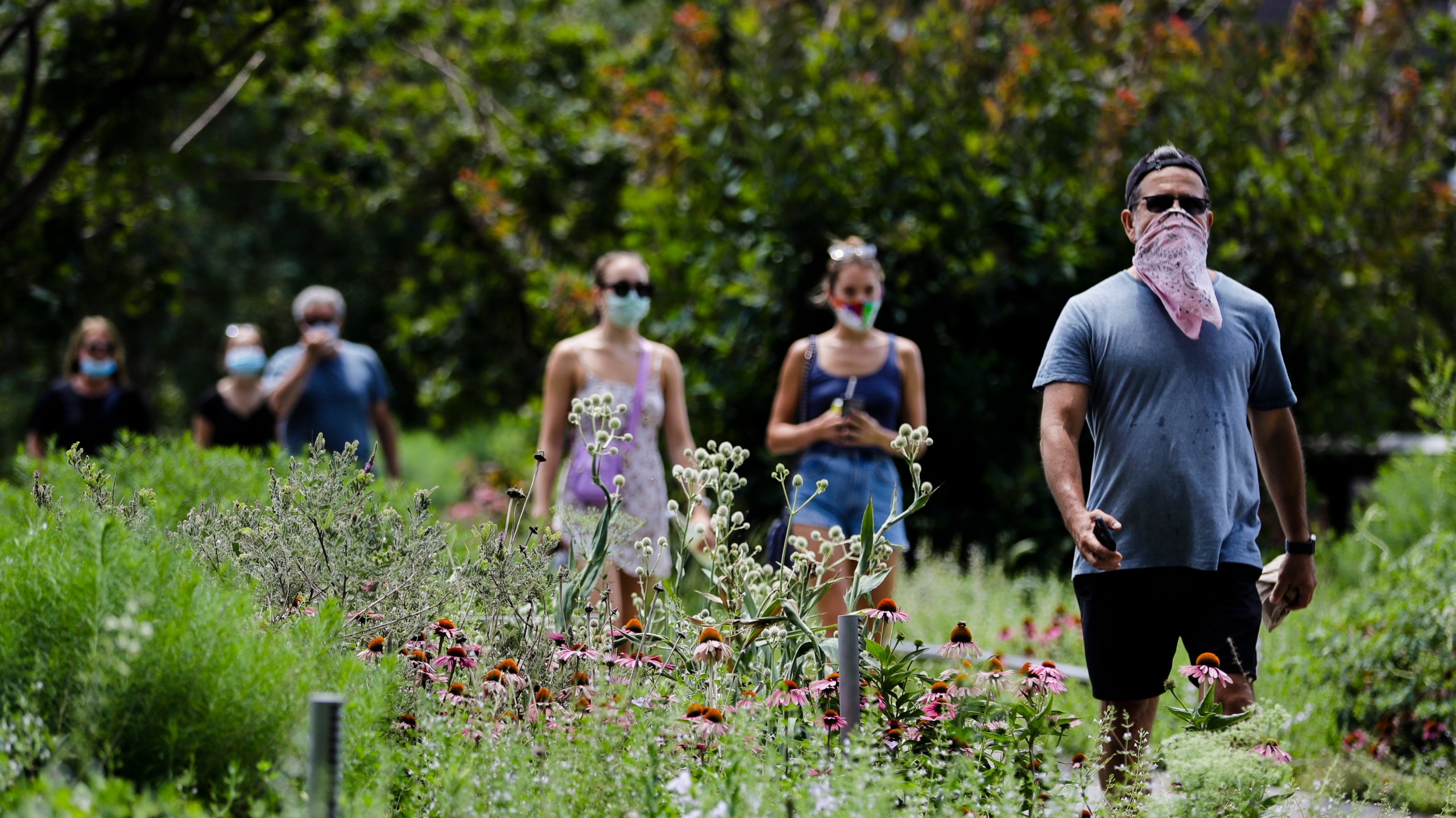 People walk along the High Line Park in New York City on July 16, 2020. (Frank Franklin II / Associated Press)