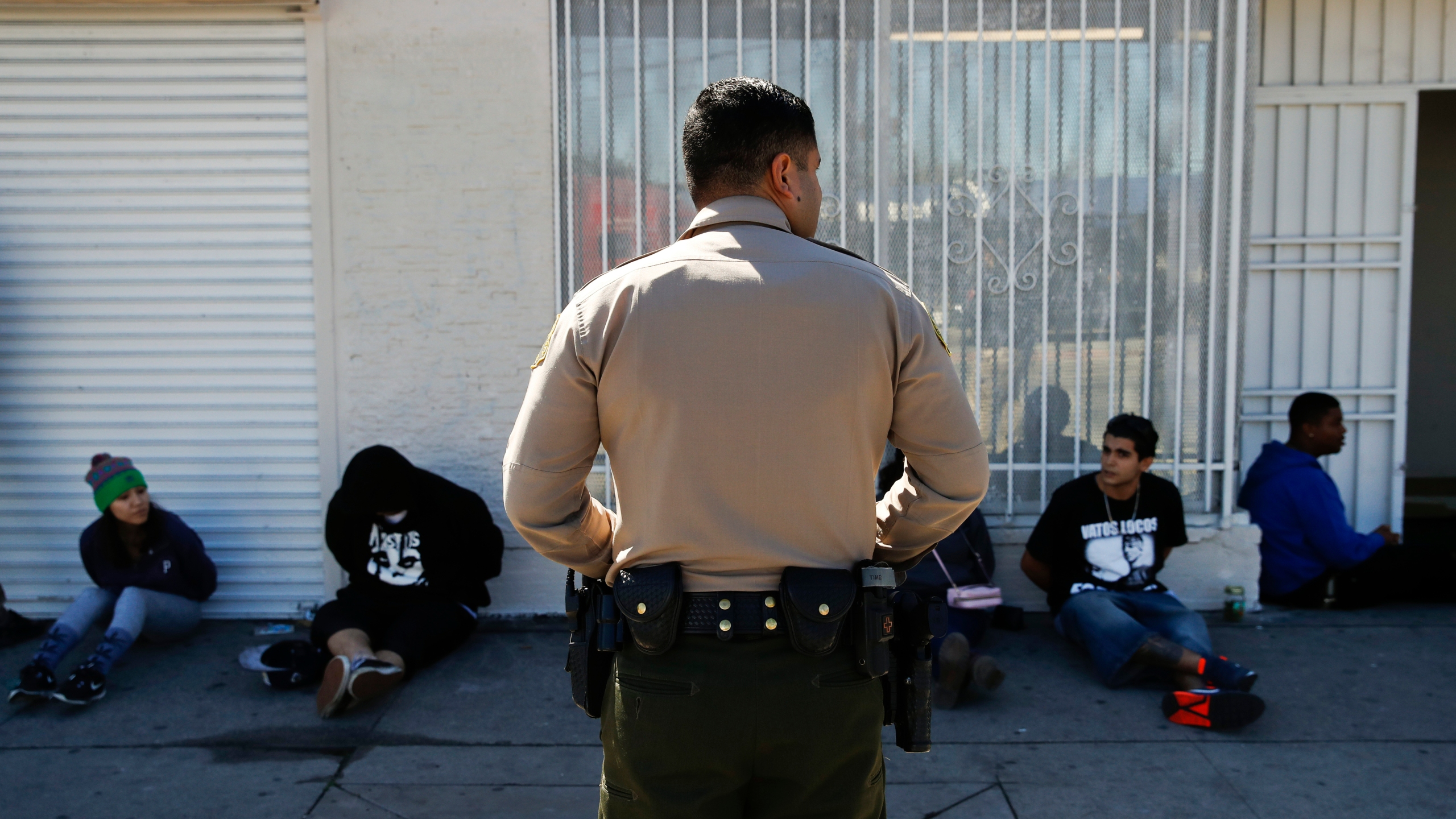 A Los Angeles County Sheriff's deputy keeps watch on a group of people apprehended at an illegal marijuana dispensary in Compton in this March 15, 2018, file photo. (Jae C. Hong / Associated Press)