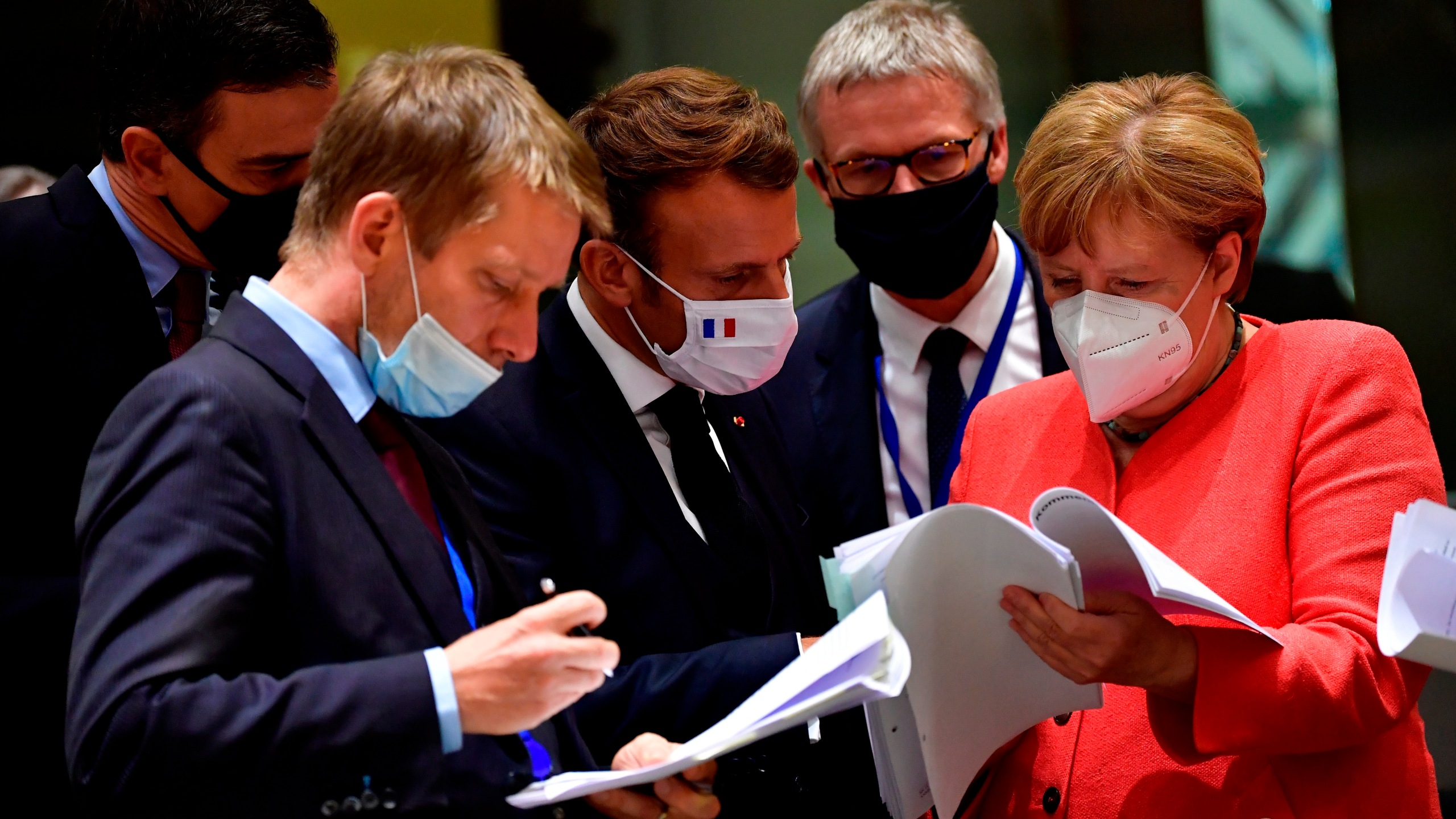 German Chancellor Angela Merkel, right, speaks with French President Emmanuel Macron, center, during a round table meeting at an EU summit in Brussels, Monday, July 20, 2020. (John Thys, Pool Photo via AP)