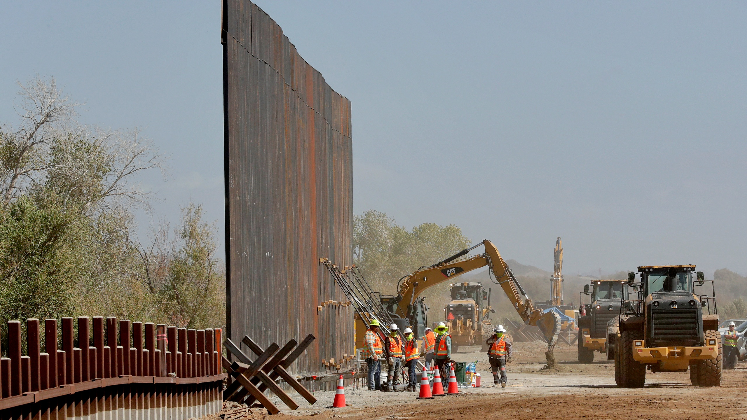 In this Sept. 10, 2019, file photo, government contractors erect a section of Pentagon-funded border wall along the Colorado River in Yuma, Arizona. (Matt York / Associated Press)