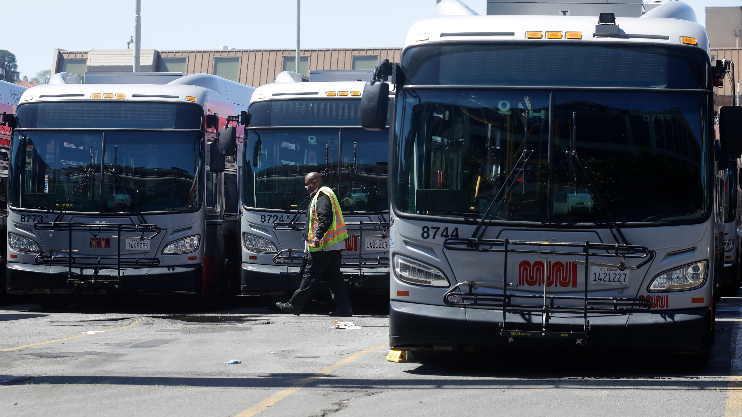 In this April 7, 2020, file photo, a Muni worker walks in front of buses at a San Francisco Municipal Transportation Agency yard in San Francisco. A San Francisco bus driver was assaulted with a wooden bat after asking several passengers to wear a mask in keeping with city health orders to combat the coronavirus. A San Francisco police spokesman said three men boarded the bus Wednesday afternoon, July 22, 2020, and refused the driver's multiple requests to put on masks. (AP Photo/Jeff Chiu, File)
