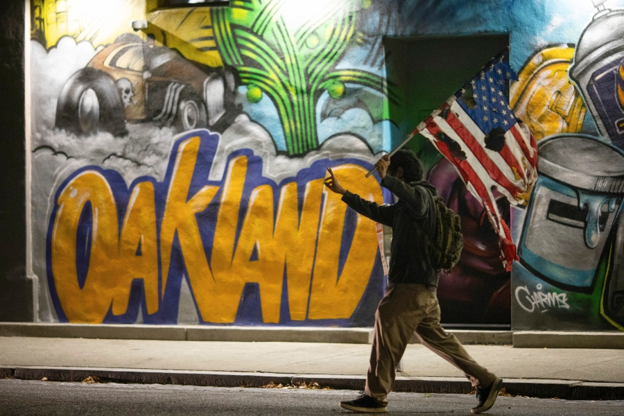 A protester holds a burnt flag in front of a mural during a protest on Saturday, July 25, 2020, in Oakland, Calif. Protesters in California set fire to a courthouse, damaged a police station and assaulted officers after a peaceful demonstration intensified late Saturday, Oakland police said. (AP Photo/Christian Monterrosa)