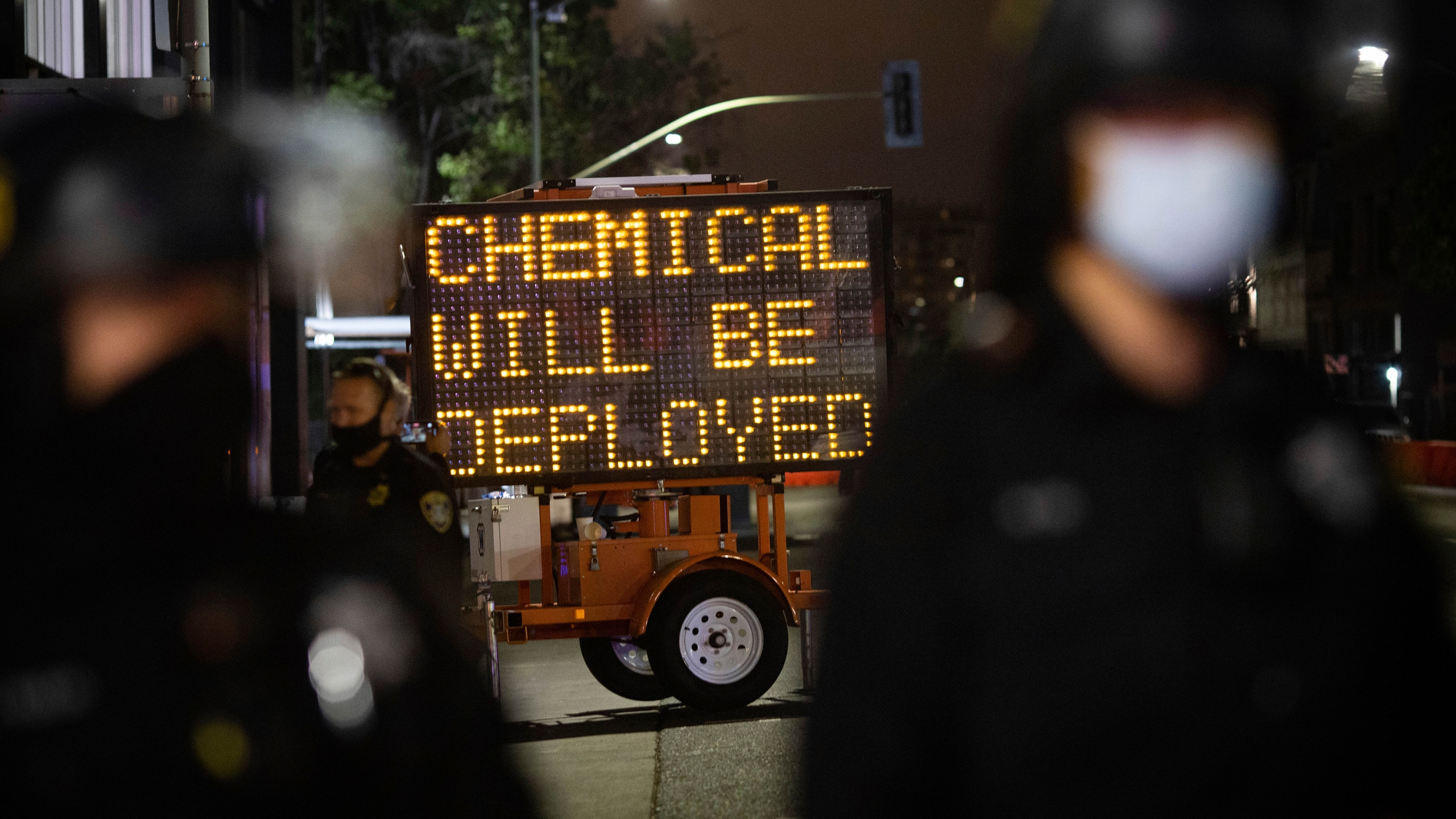 A road sign warns protesters of the use of chemical agents for failure to disperse after a protest was declared unlawful on Saturday, July 25, 2020, in Oakland. (AP Photo/Christian Monterrosa)
