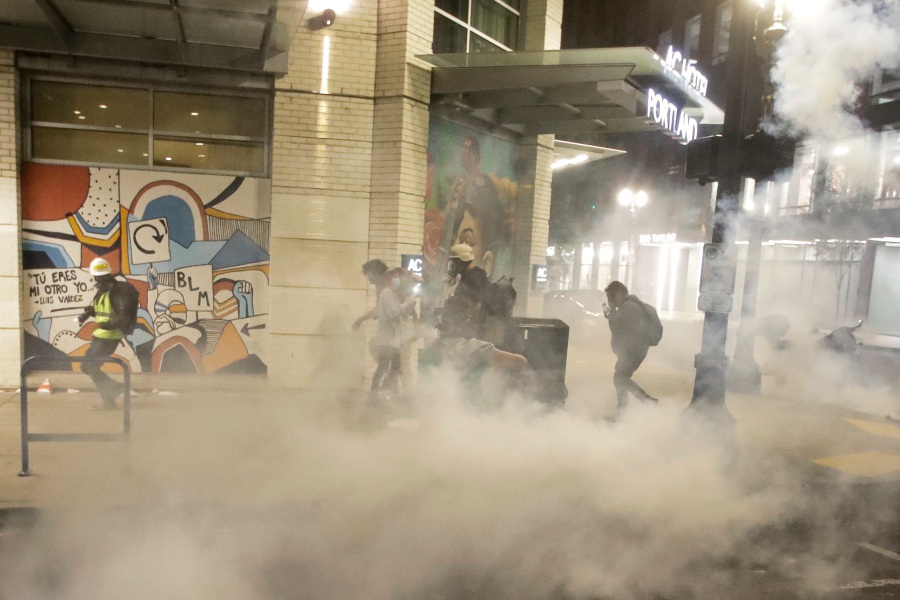 Demonstrators walk away from tear gas deployed by federal officers during a Black Lives Matter protest Sunday, July 26, 2020, in Portland, Ore. (AP Photo/Marcio Jose Sanchez)