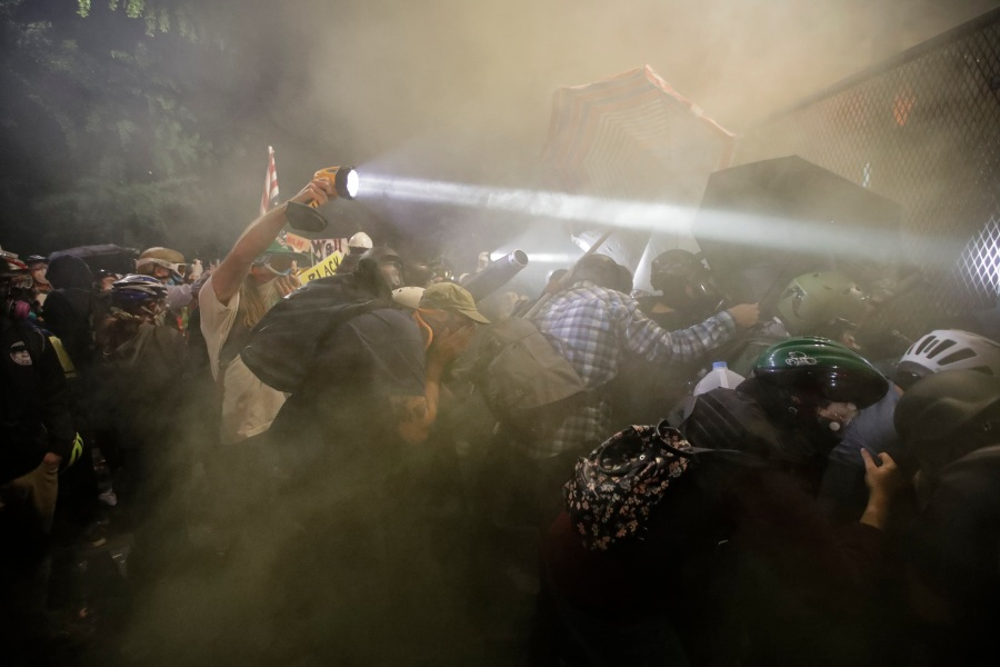 Demonstrators push on a fence as tear gas is deployed during a Black Lives Matter protest at the Mark O. Hatfield United States Courthouse Saturday, July 25, 2020, in Portland, Ore. (AP Photo/Marcio Jose Sanchez)