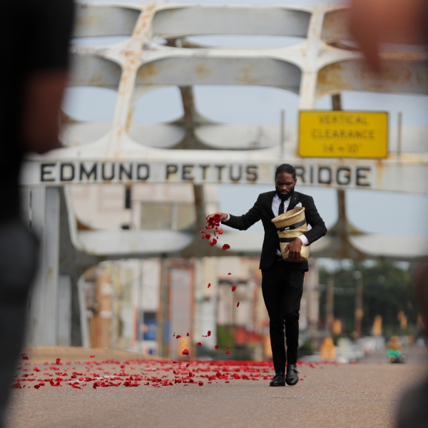 A man places flower petals on the Edmund Pettus Bridge ahead of Rep. John Lewis' casket crossing during a memorial service for Lewis, Sunday, July 26, 2020, in Selma, Ala. (AP Photo/Brynn Anderson)