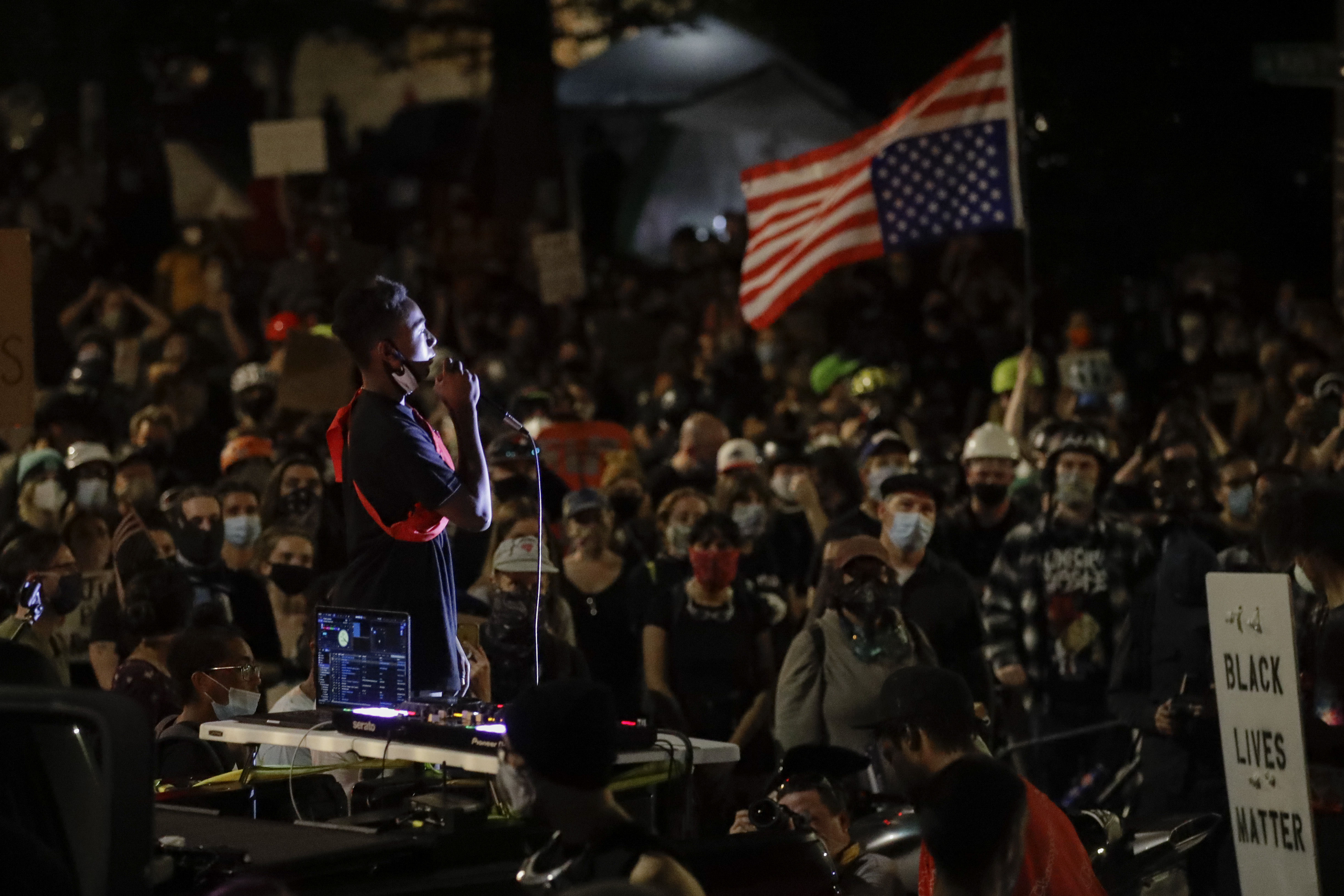 A demonstrator speaks to a crowd from the bed of a pickup truck during a Black Lives Matter protest at the Mark O. Hatfield United States Courthouse Sunday, July 26, 2020, in Portland, Ore. (AP Photo/Marcio Jose Sanchez)