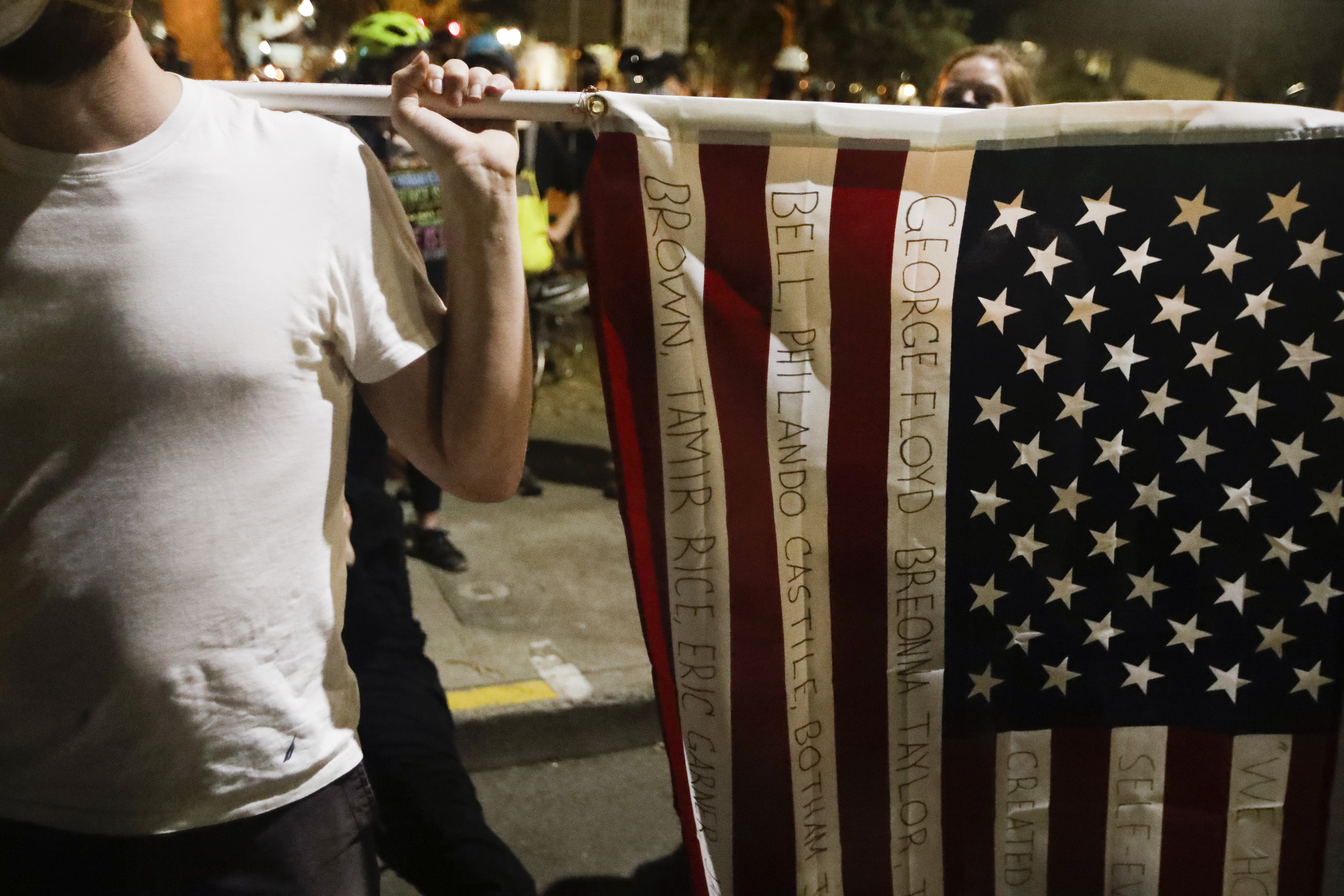 A demonstrator holds an American flag with names of people killed by police during a Black Lives Matter protest at the Mark O. Hatfield United States Courthouse Sunday, July 26, 2020, in Portland, Ore. (AP Photo/Marcio Jose Sanchez)