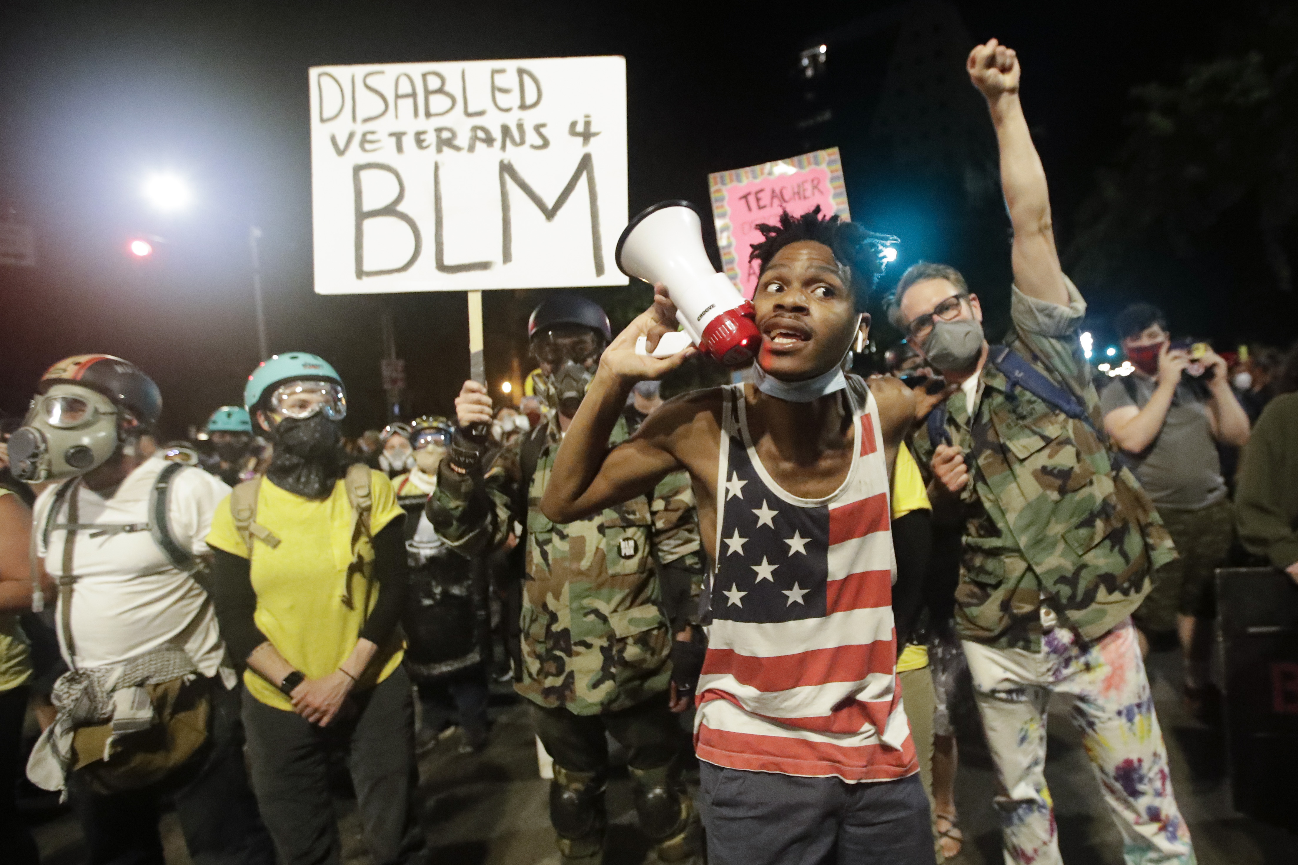 A demonstrator shouts slogans using a bullhorn next to a group of military veterans during a Black Lives Matter protest at the Mark O. Hatfield United States Courthouse Sunday, July 26, 2020, in Portland, Ore. (AP Photo/Marcio Jose Sanchez)