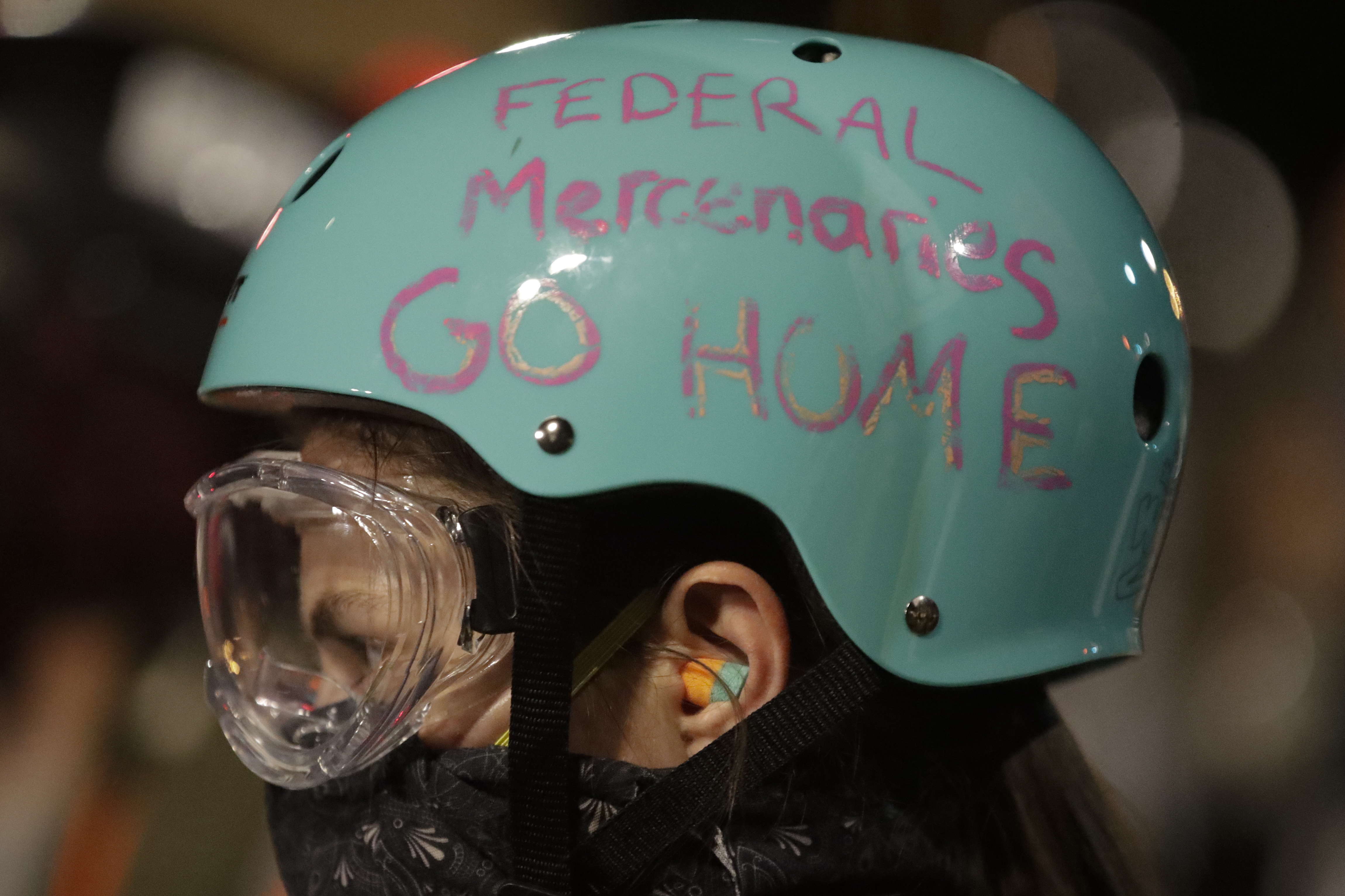 """A demonstrator's protective helmet reads """"Federal Mercenaries Go Home"""" during a Black Lives Matter protest at the Mark O. Hatfield United States Courthouse Sunday, July 26, 2020, in Portland, Ore. (AP Photo/Marcio Jose Sanchez)"""