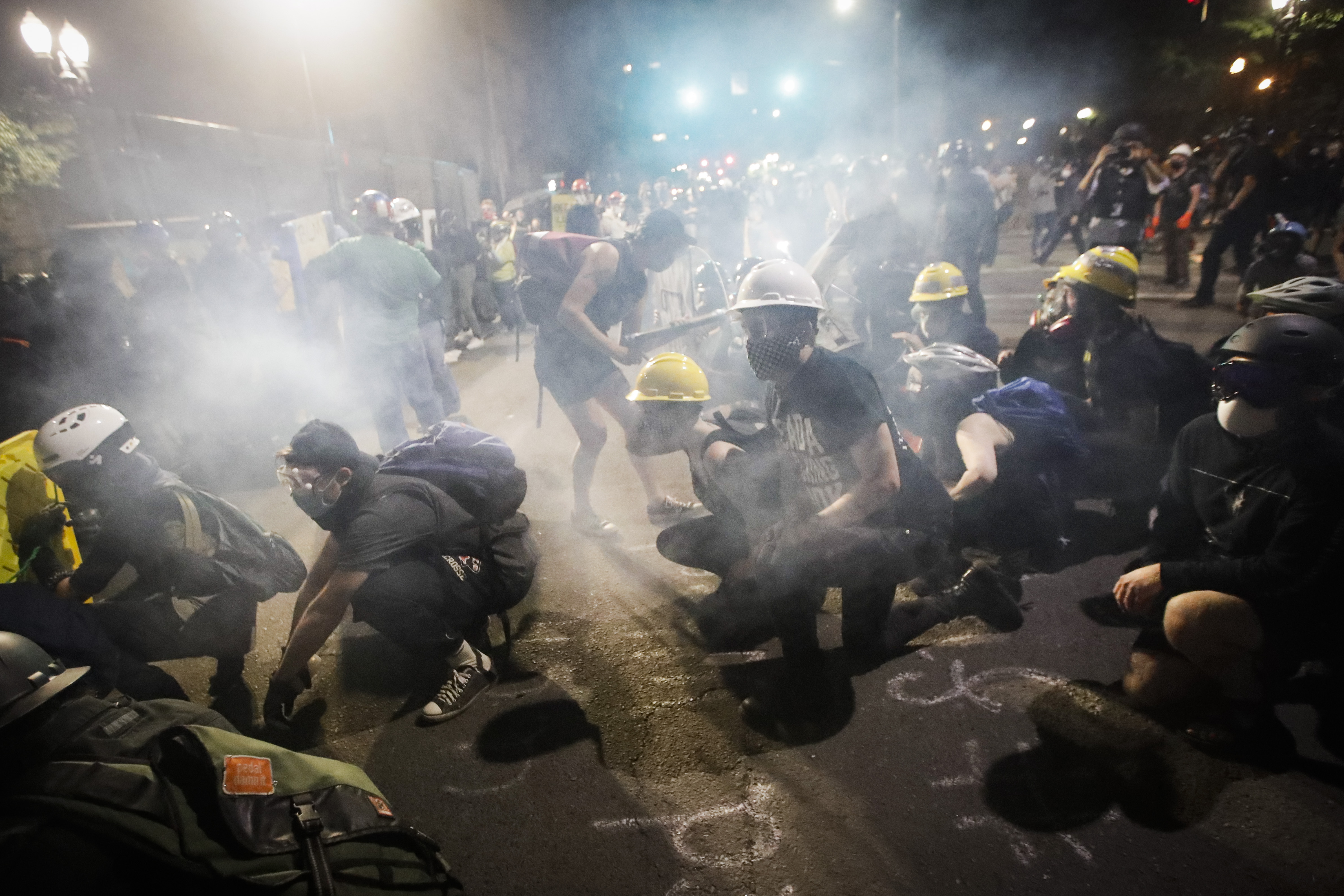 Demonstrators sit and kneel as tear gas fills the air during a Black Lives Matter protest at the Mark O. Hatfield United States Courthouse Sunday, July 26, 2020, in Portland, Ore. (AP Photo/Marcio Jose Sanchez)