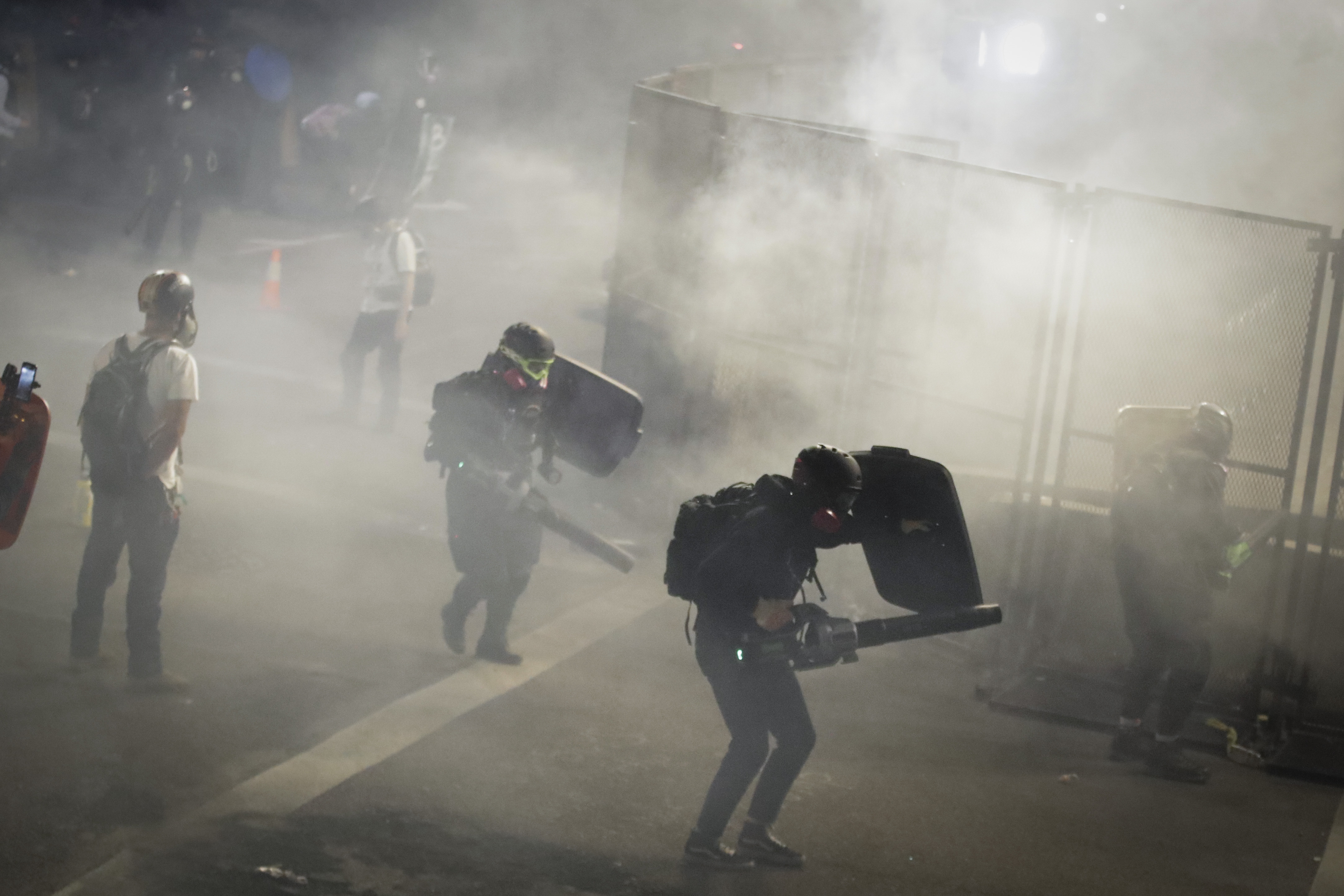 Demonstrators use leaf blowers to try to blow back tear gas launched by federal officers during a Black Lives Matter protest at the Mark O. Hatfield United States Courthouse Sunday, July 26, 2020, in Portland, Ore. (AP Photo/Marcio Jose Sanchez)