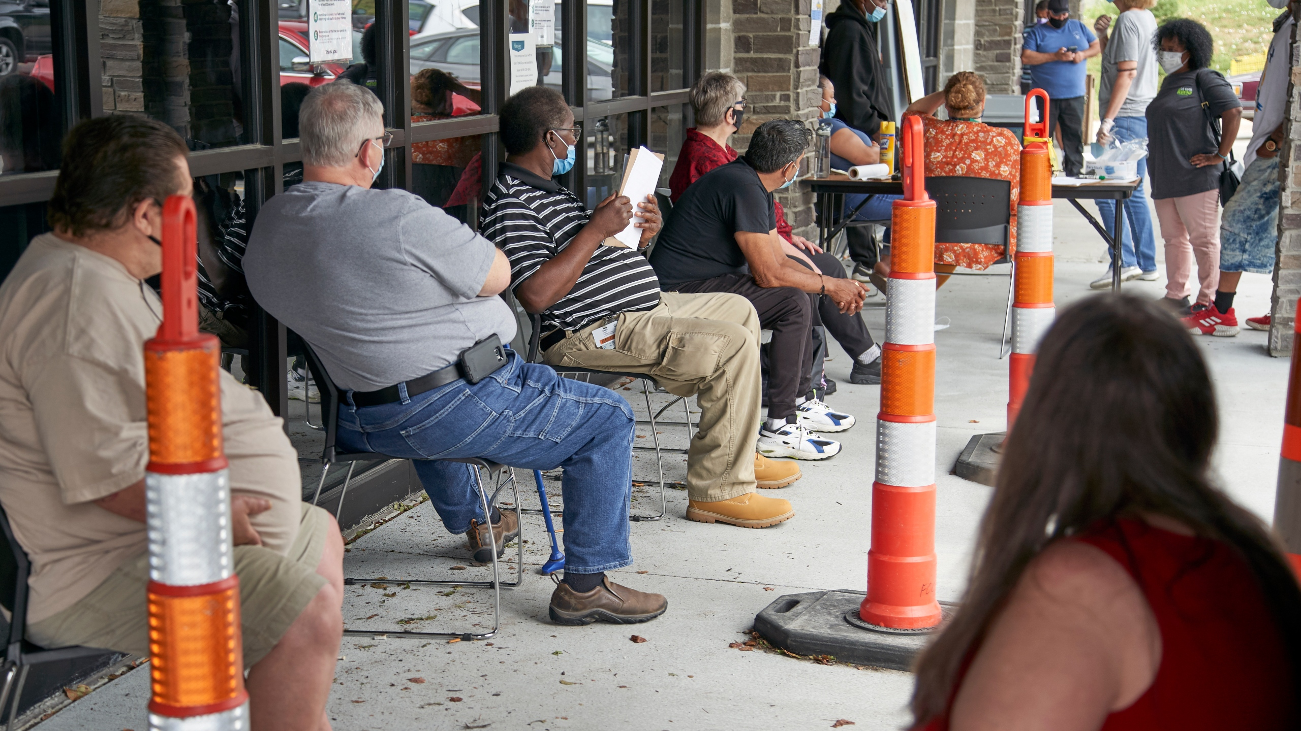In this July 15, 2020, file photo, job seekers exercise social distancing as they wait to be called into the Heartland Workforce Solutions office in Omaha, Neb. A Republican proposal to slash the $600 weekly benefit boost for those left jobless because of the coronavirus shutdown could result in weeks or even months of delayed payments in some states. (AP Photo/Nati Harnik, File)
