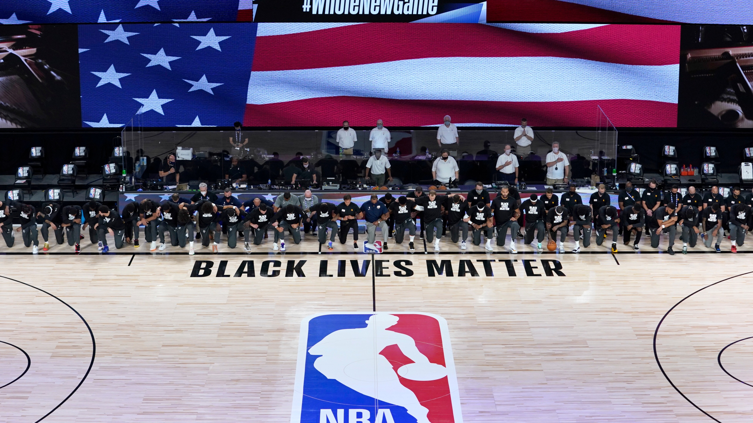 Members of the New Orleans Pelicans and Utah Jazz kneel together around the Black Lives Matter logo on the court during the national anthem before the start of an NBA basketball game on July 30, 2020, in Lake Buena Vista, Fla. (AP Photo/Ashley Landis, Pool)