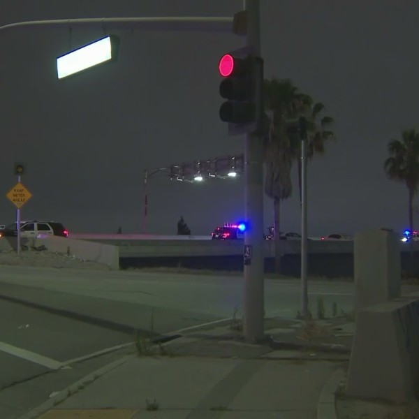 Officers investigate the scene where they said a driver who led two pursuits jumped over a wall near the 91 Freeway in Anaheim on July 23, 2020. (KTLA)