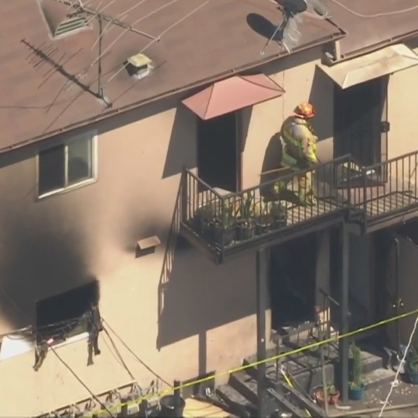 Authorities investigate the scene of a deadly fire at a Pasadena apartment building on July 29, 2020. (KTLA)