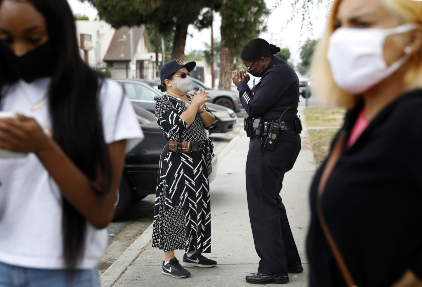 Emada Tingirides, deputy chief of the LAPD's new community policing bureau, chats with Augie Lopez of the city's Housing Authority at Nickerson Gardens in Watts in this undated photo. (Christina House / Los Angeles Times)