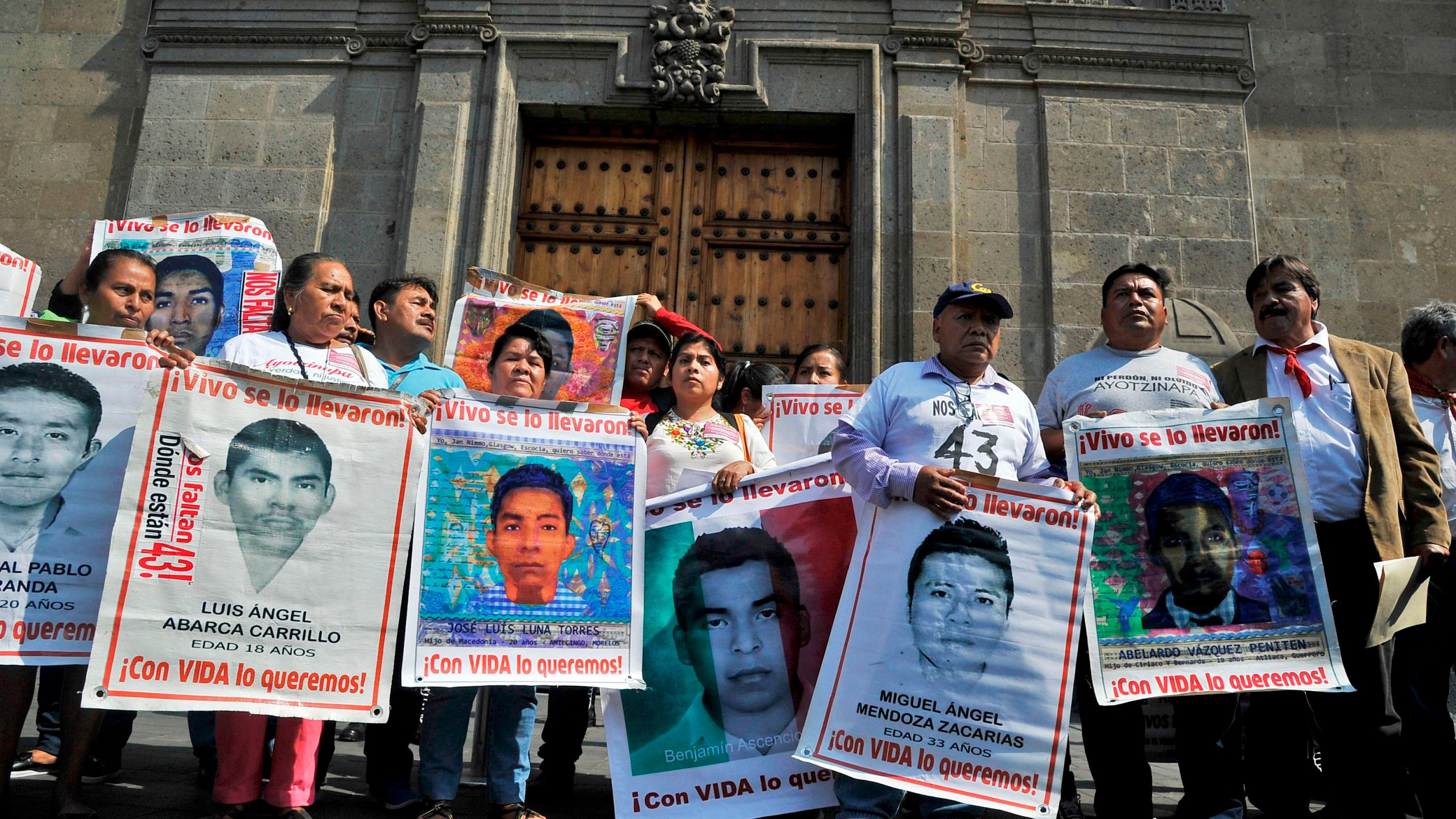 Relatives of the 43 missing students of the teacher's training school of Ayotzinapa pose with their portraits after a meeting with Mexico's President Manuel Lopez Obrador at the National Palace in Mexico City on Nov. 11, 2019. (Claudio Cruz / AFP / Getty Images)